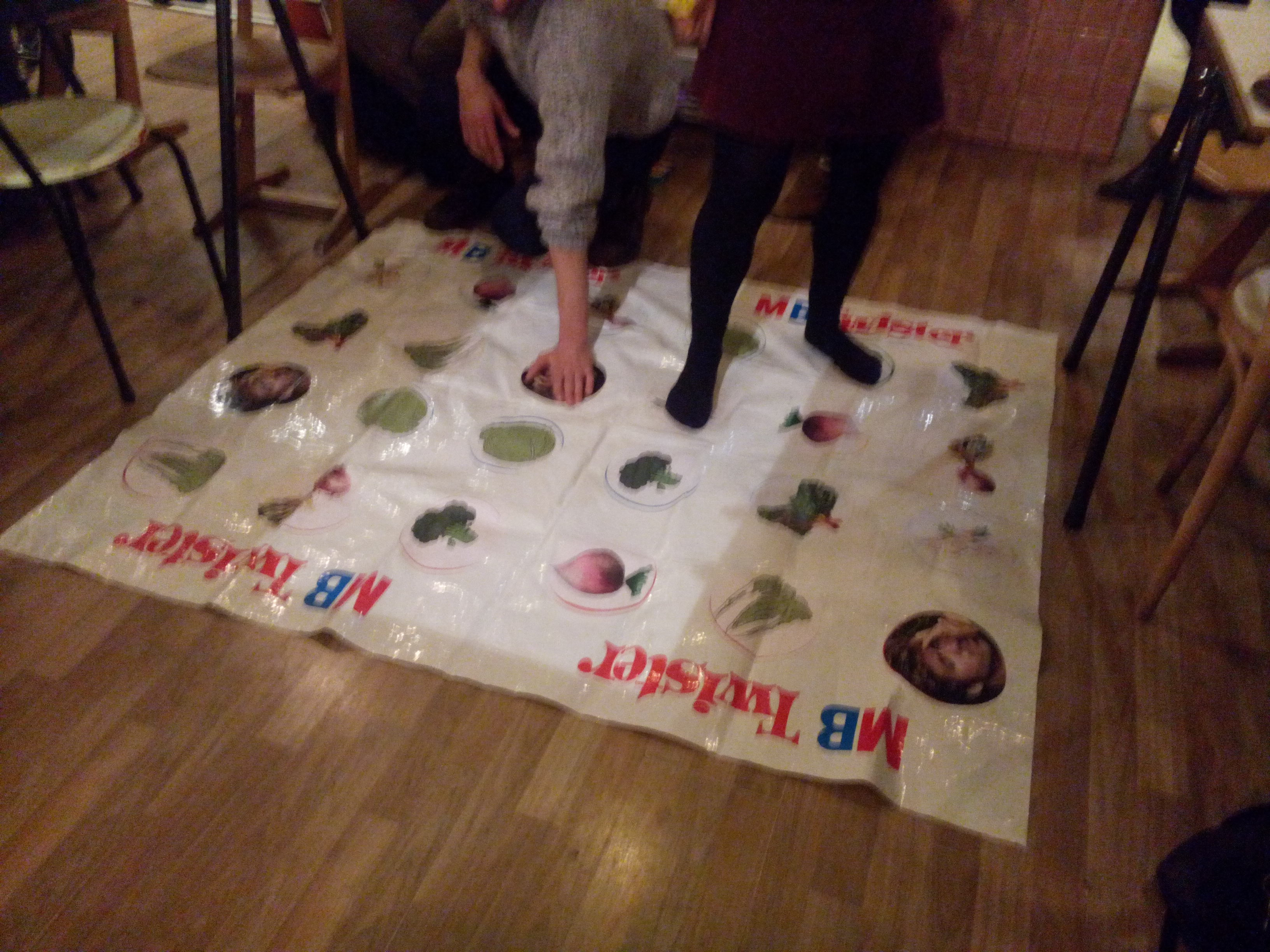 A Twister mat on the floor with people playing. The images are vegetables and George Michael's face.