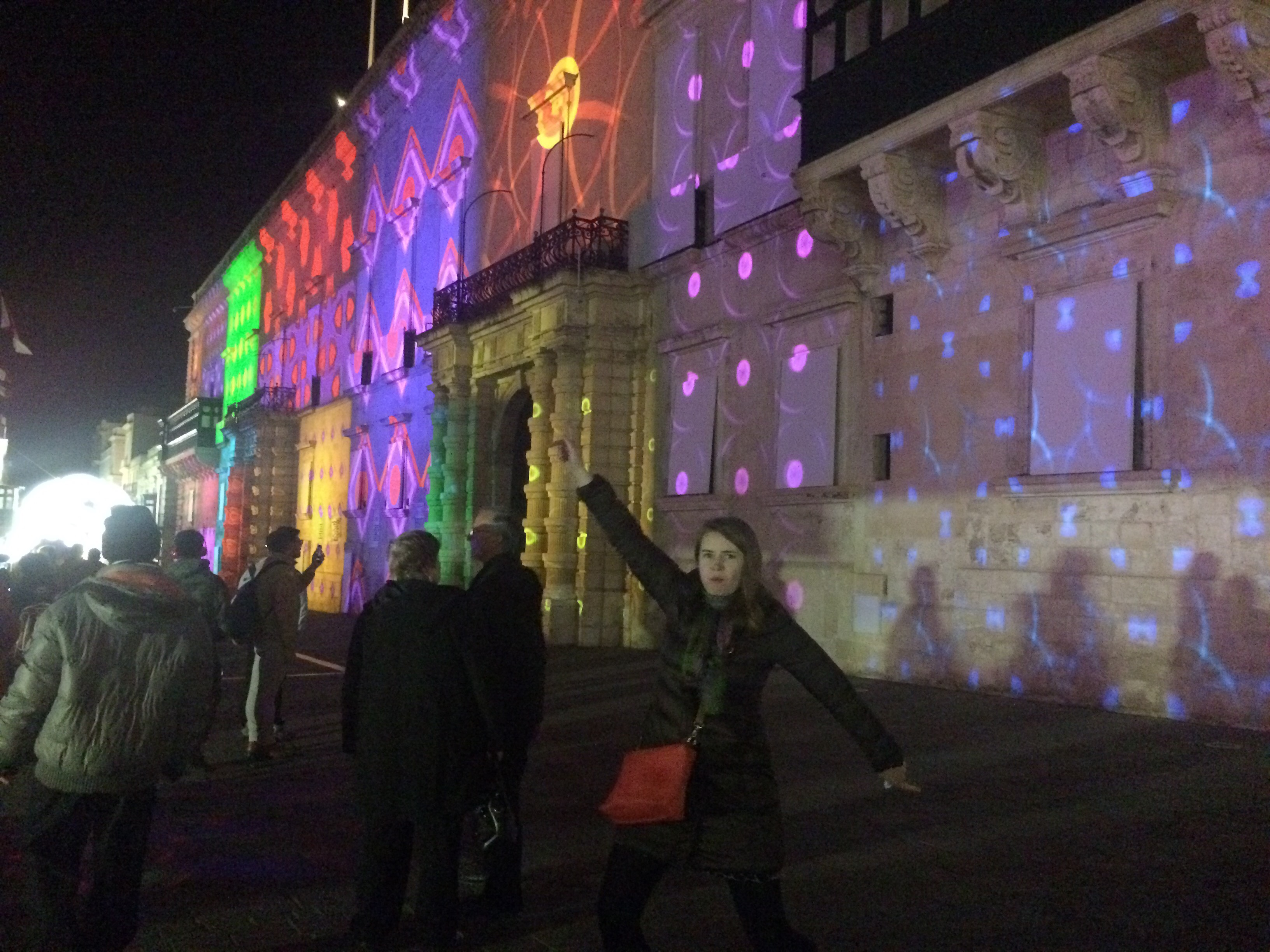 Coloured lights projected on the side of a building, with a Liz in the foreground