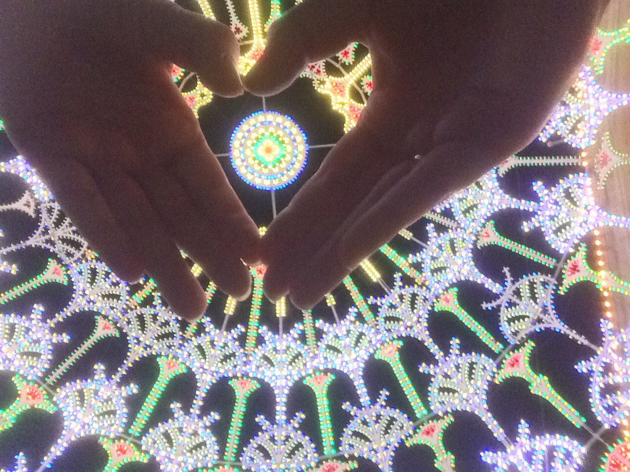 Purple and yellow patterned lights from below, with hands making a heart shape