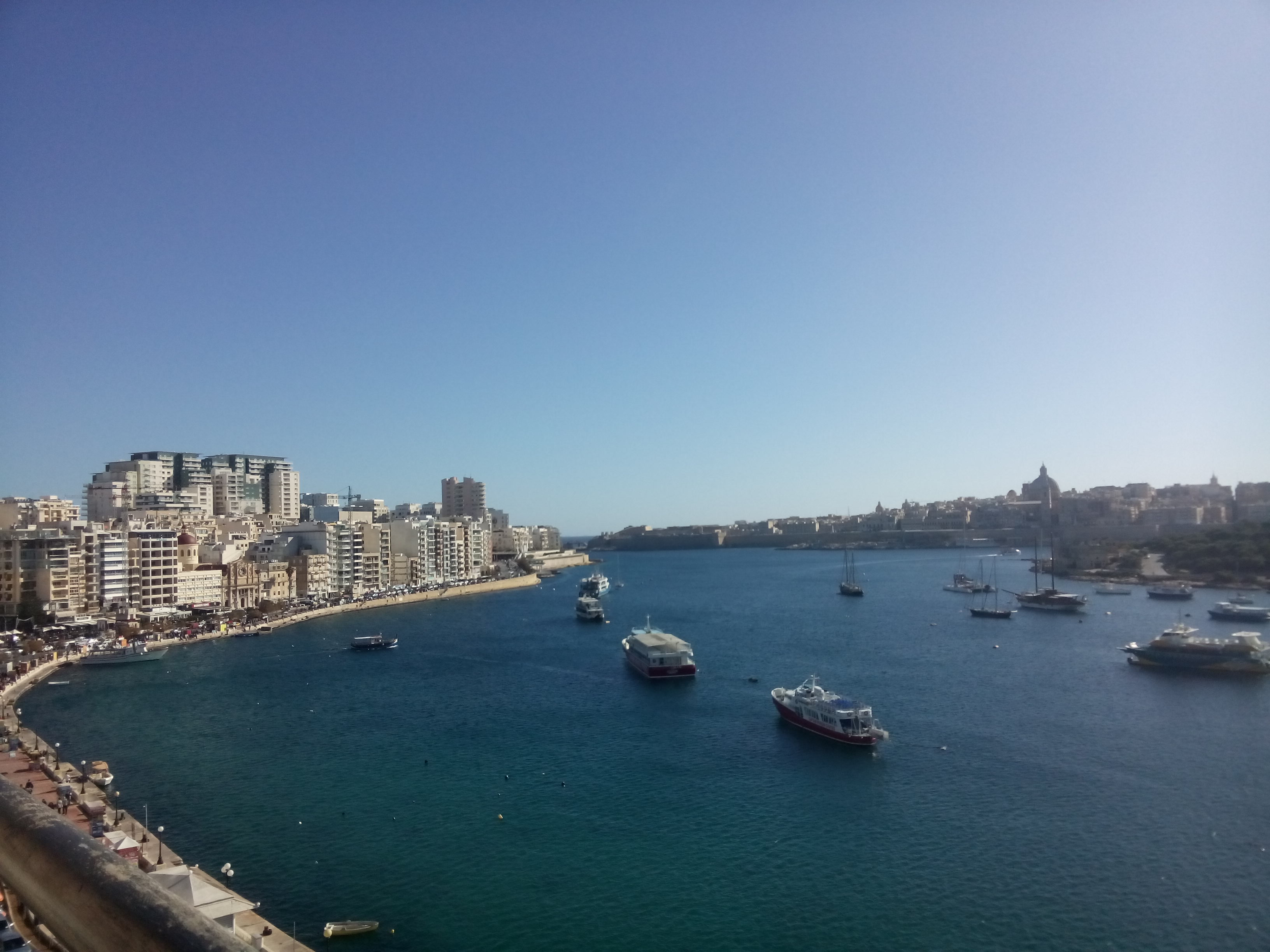 A view over a harbour with blue sea and sky