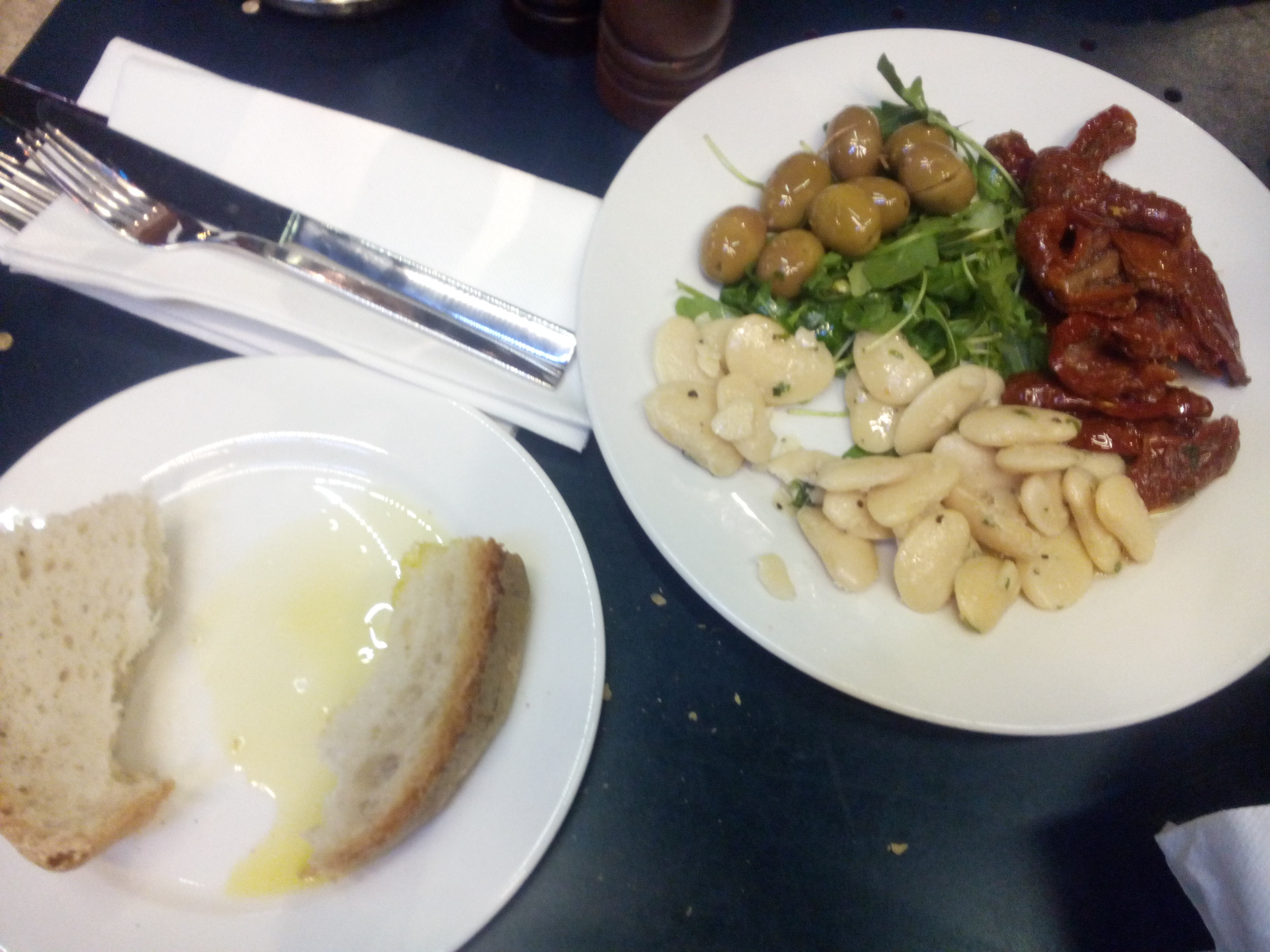 Two plates, one with bread and oil, the other with white beans, red sundried tomatoes and green olives