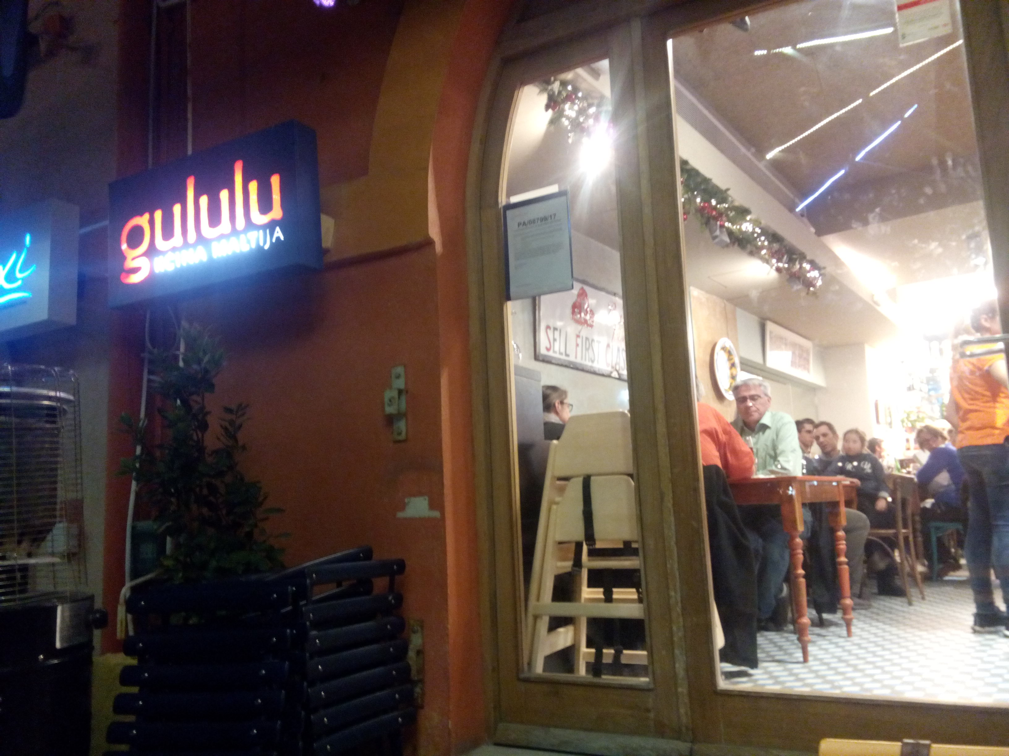 A lit sign reading 'gululu' next to the well-lit restaurant entrance