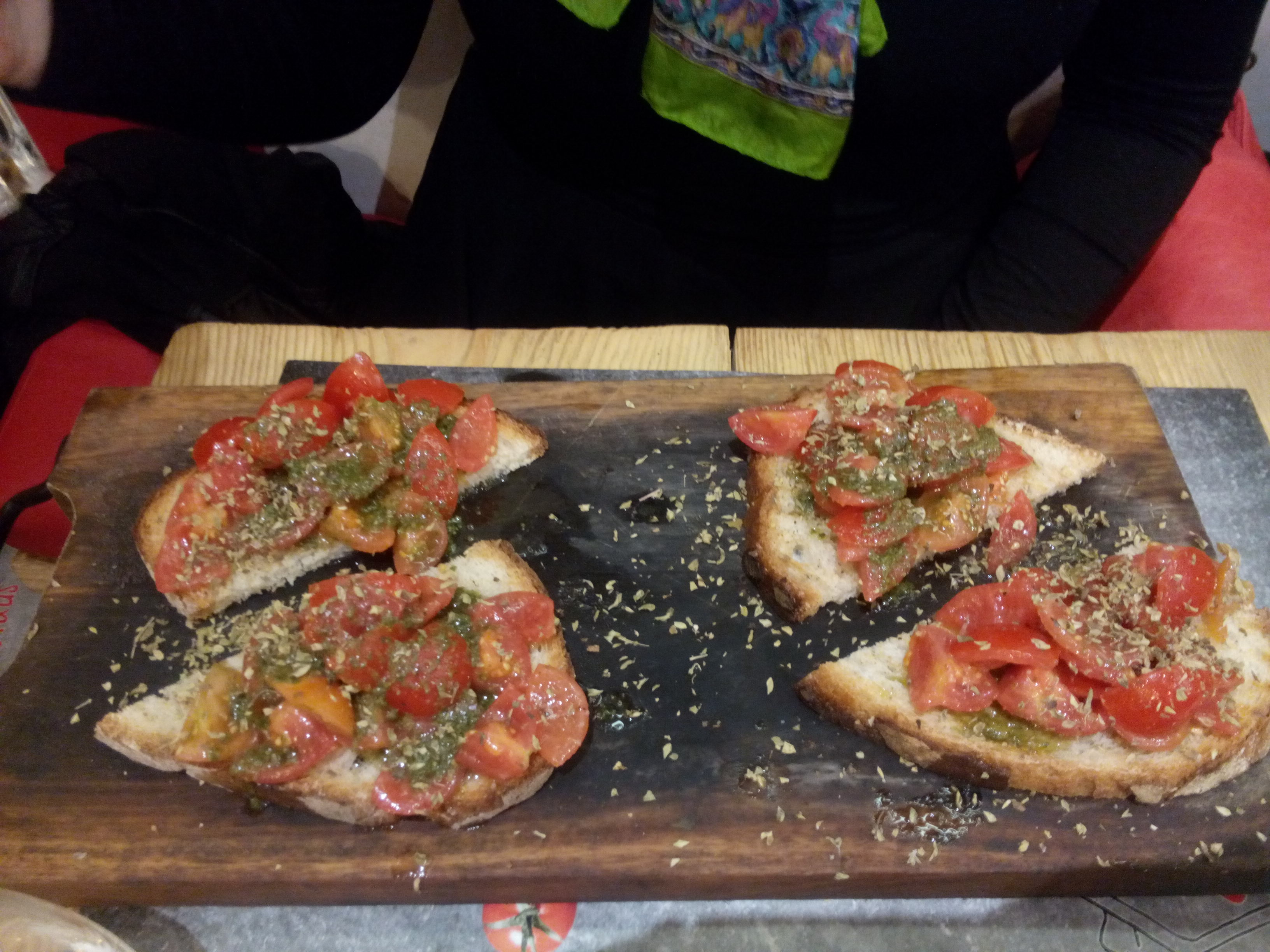 A wooden board with four pieces of tomato-topped bruschetta