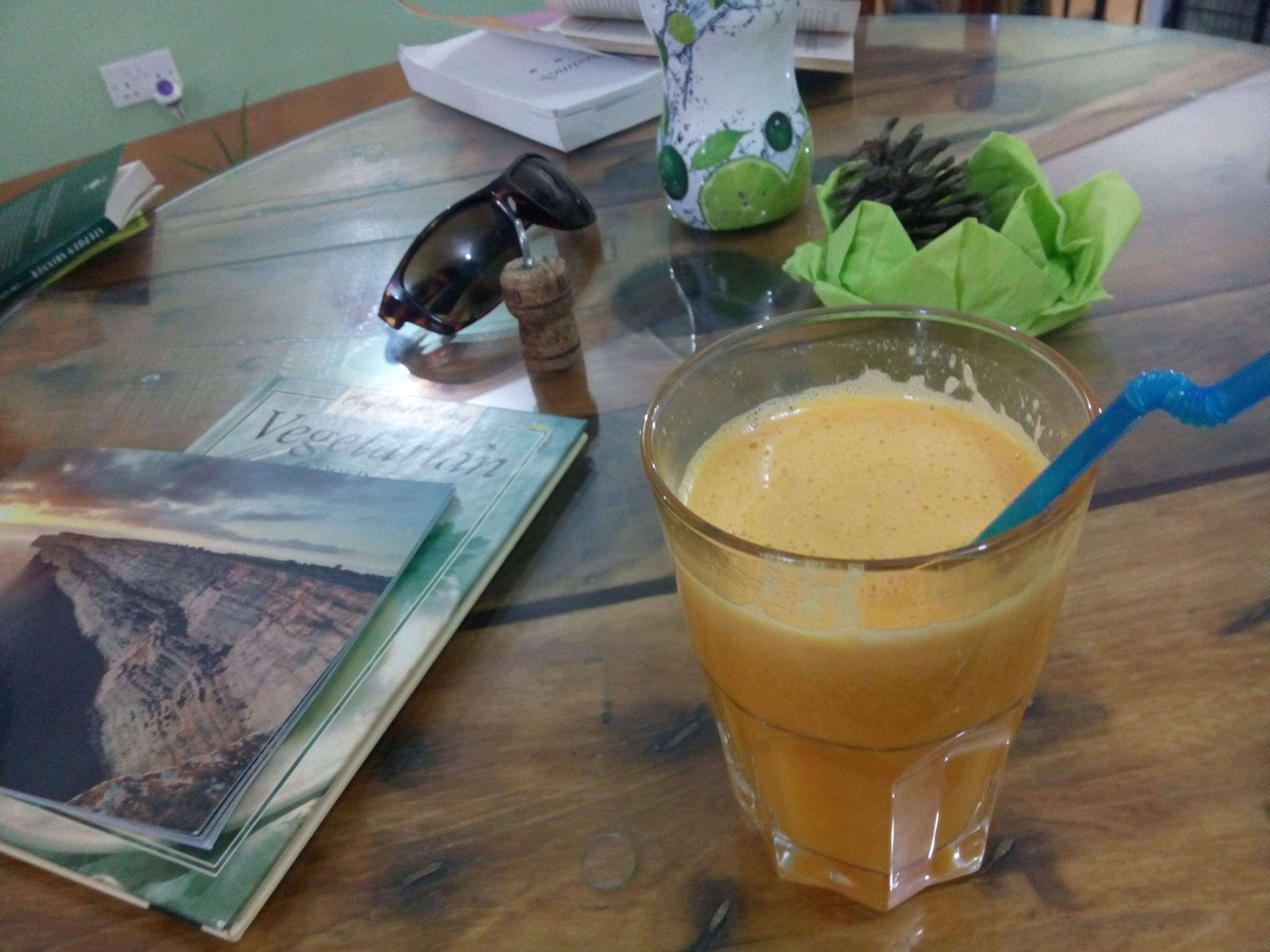 An orange smoothie in a glass on a wooden table, beside a vegetarian cookbook