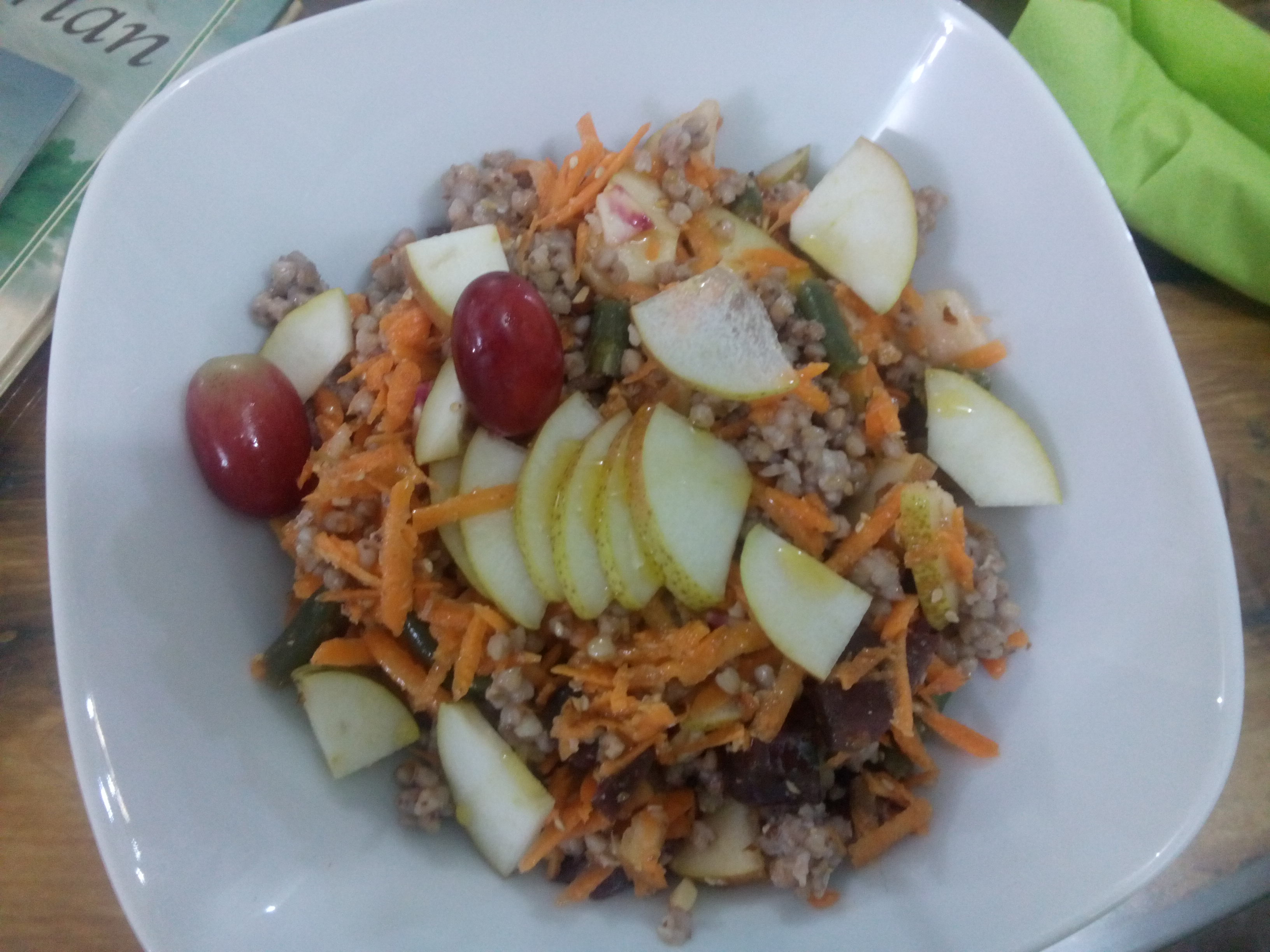 A white dish with grains, sliced pear, tomatoes and shredded carrots