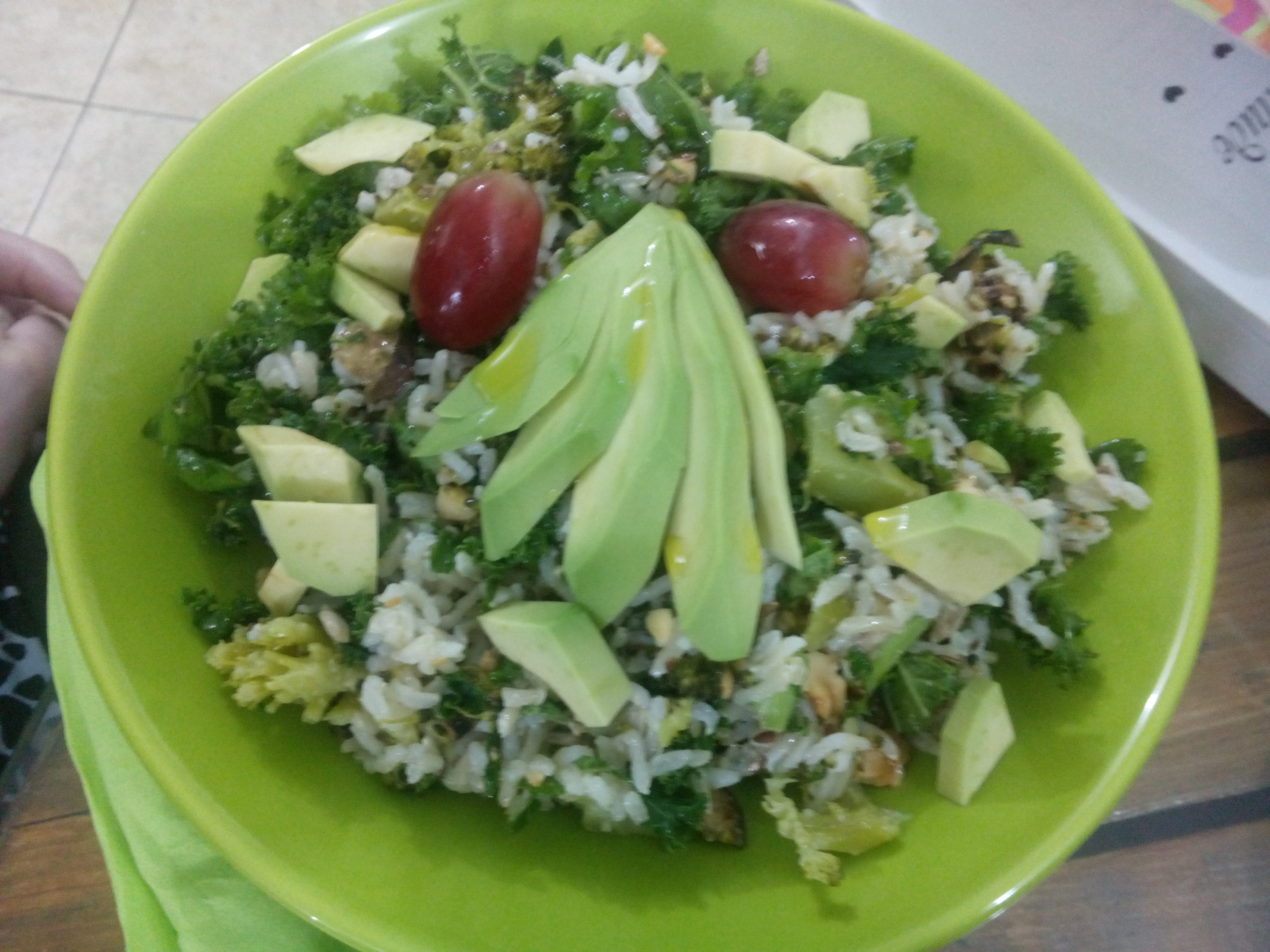 A green dish with brown rice, red grapes and avocado
