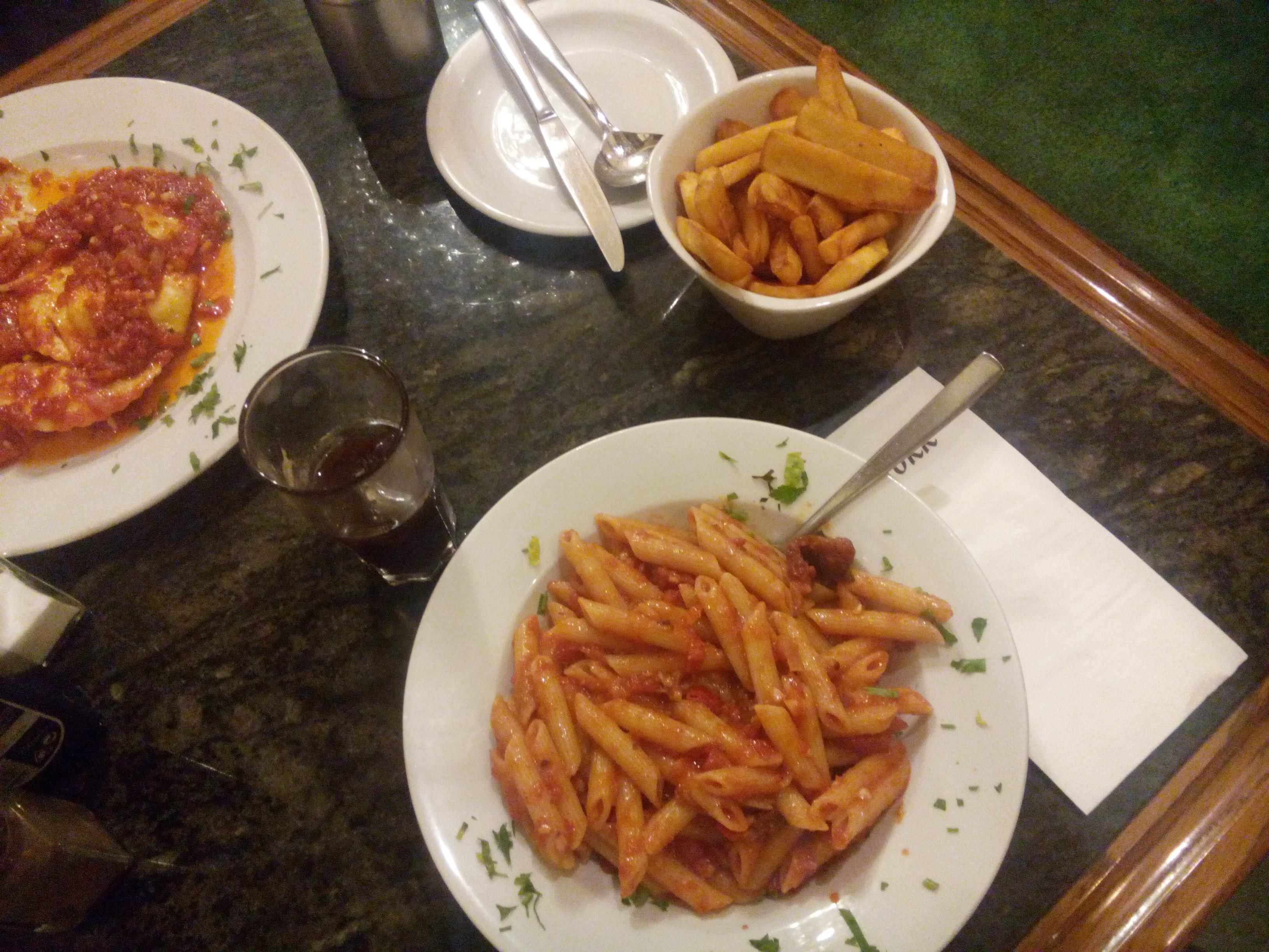 A table with two pasta dishes with tomato sauce, and a small bowl of chips