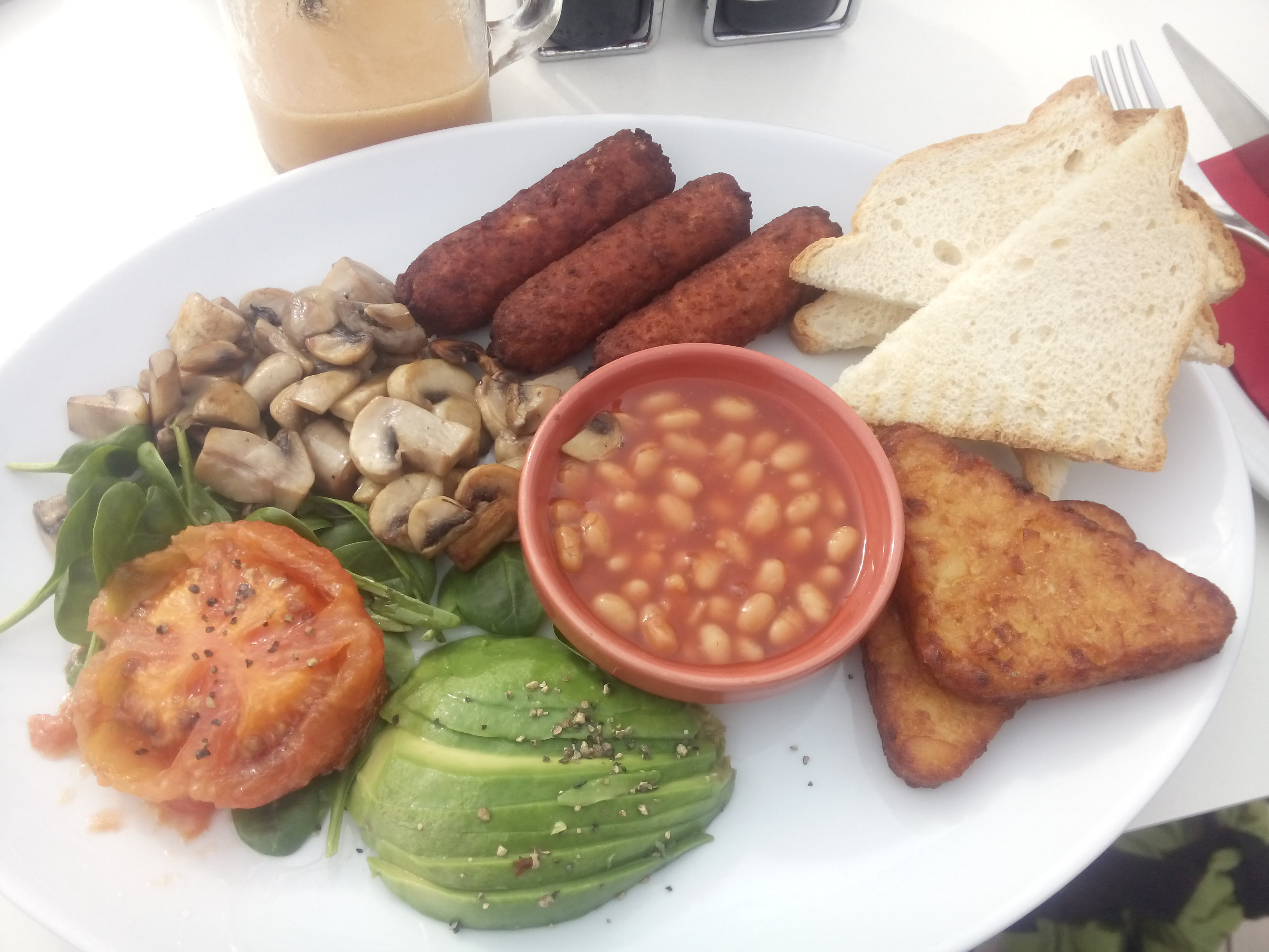 A white plate with toast, sausages, beans, hash browns, tomato, mushrooms, spinach and avocado