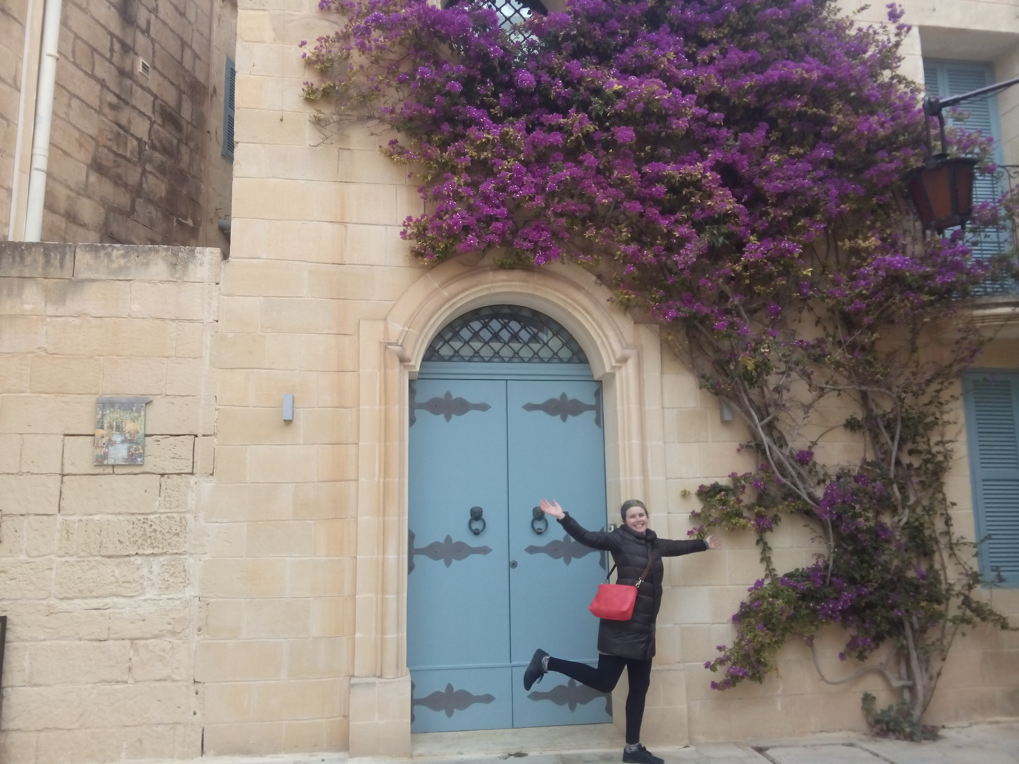 A woman in a black jacket with a red purse dances in front of a blue doorway, sandstone wall, with overhanging pink flowers