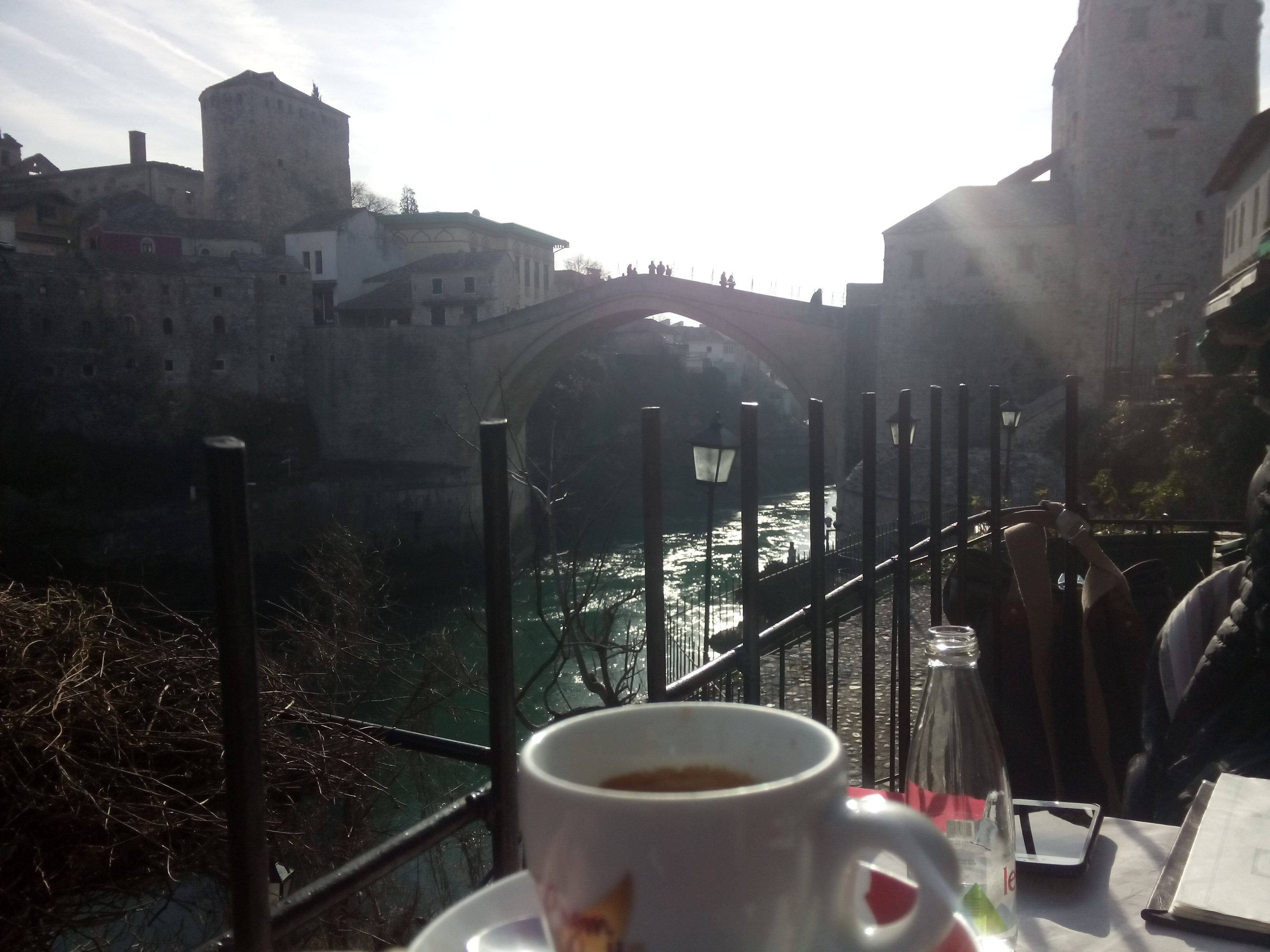 A whit eexpresso cup in the foreground with the river and Mostar bridge in the background