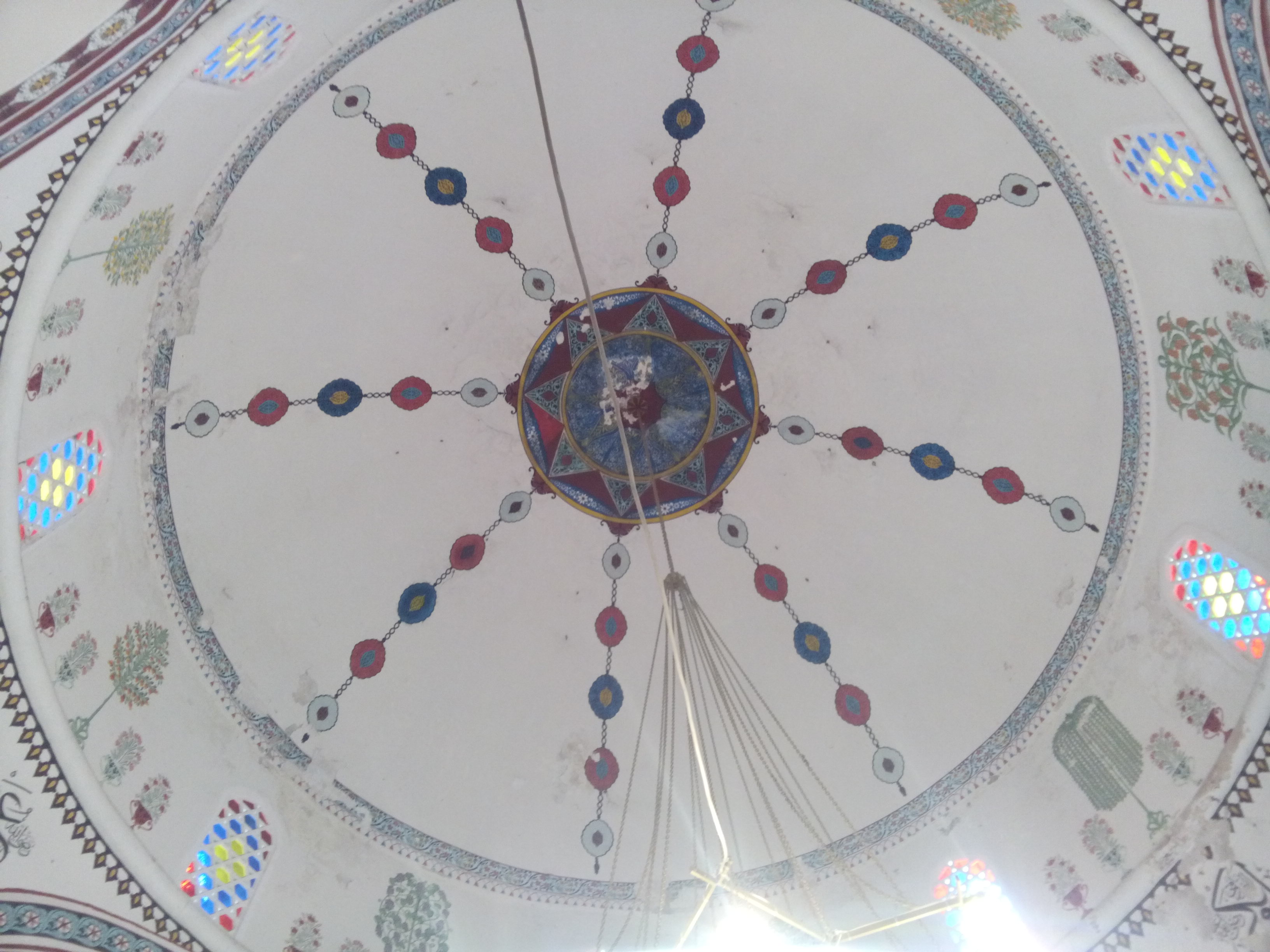 A domed white ceiling with some colourd shapes, from below