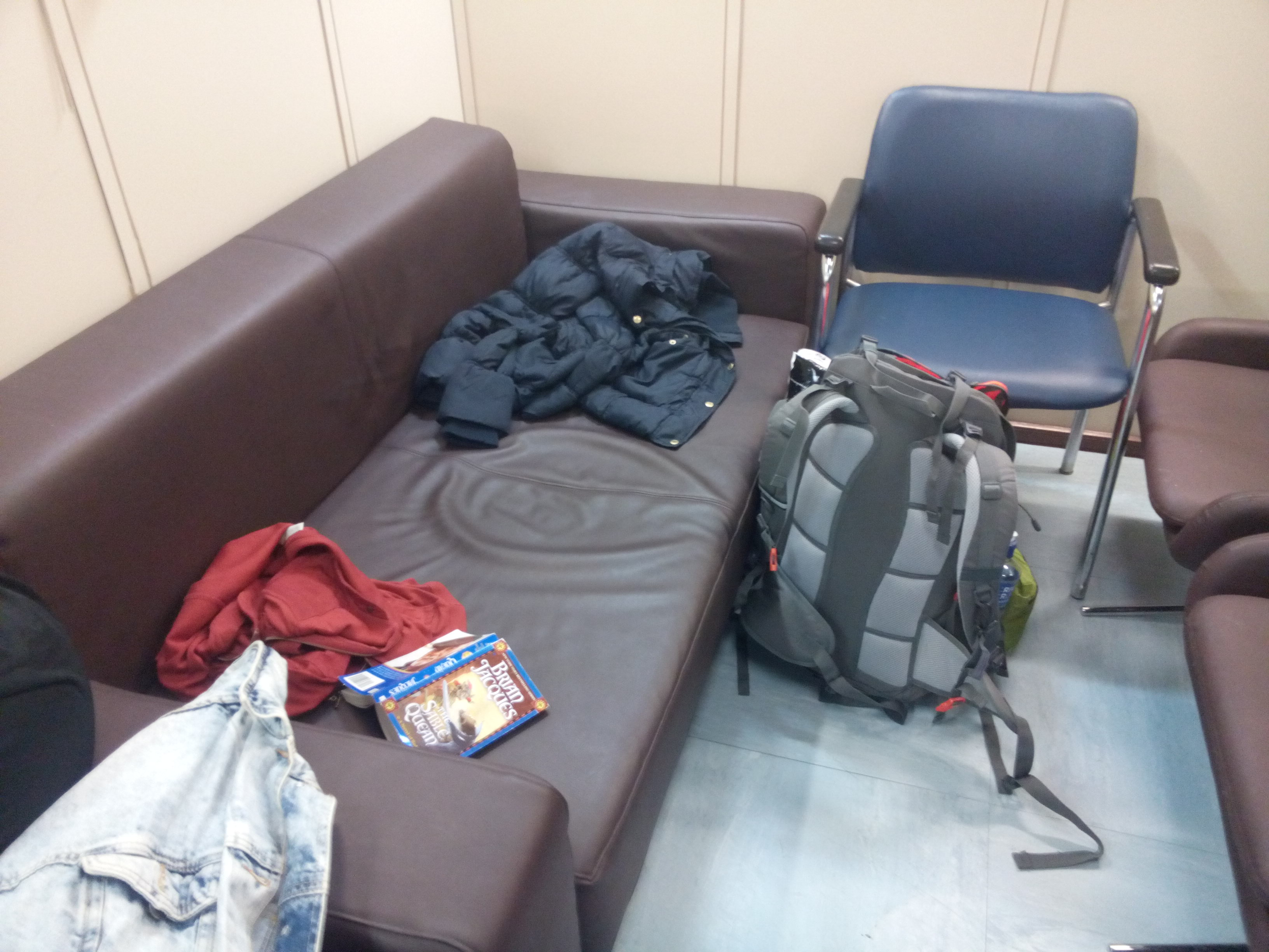 A brown sofa with blue and red coats on; a backpack on the floor by a chair