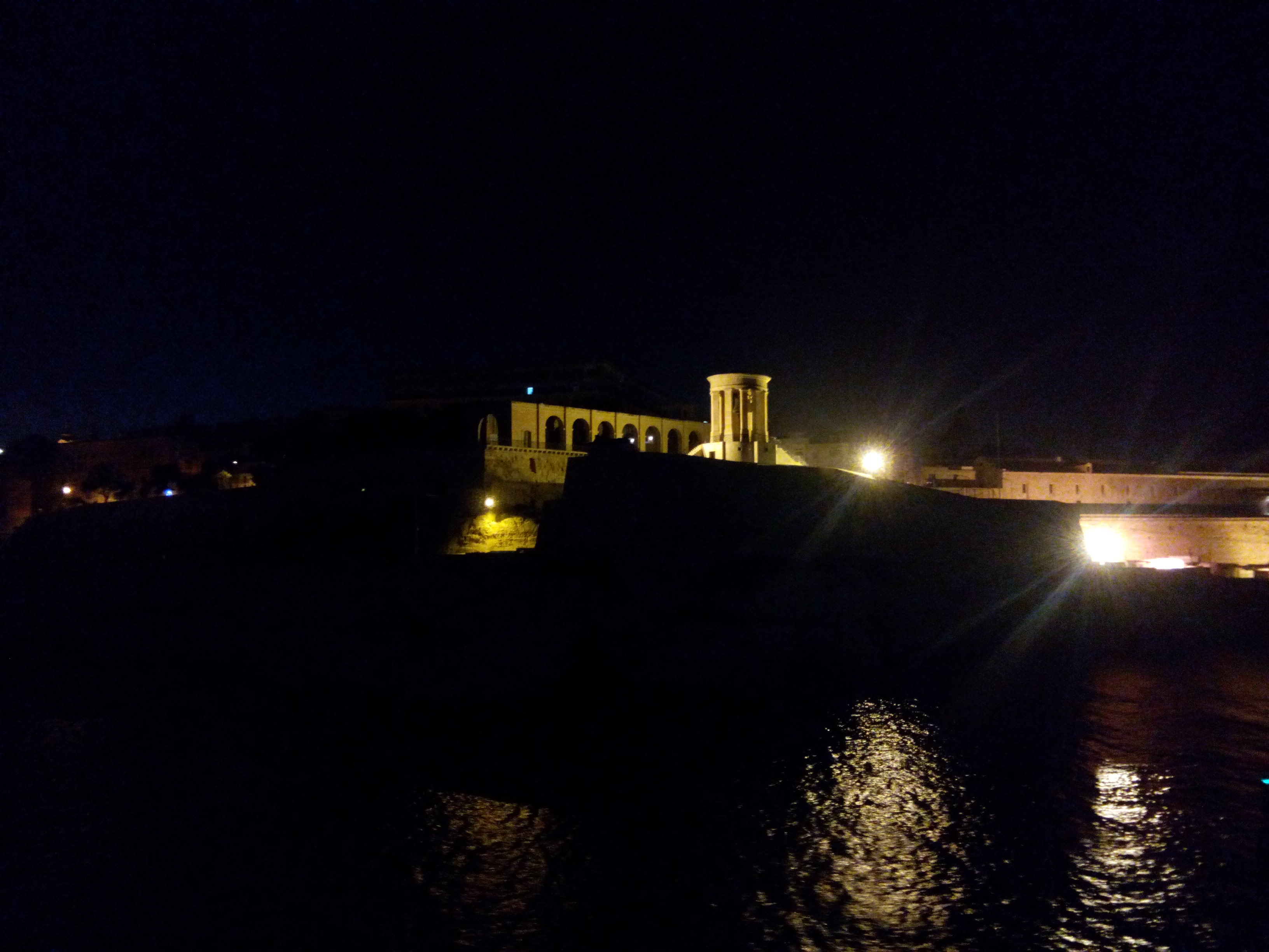 Black sky and water, with an orange-lit fort in the center