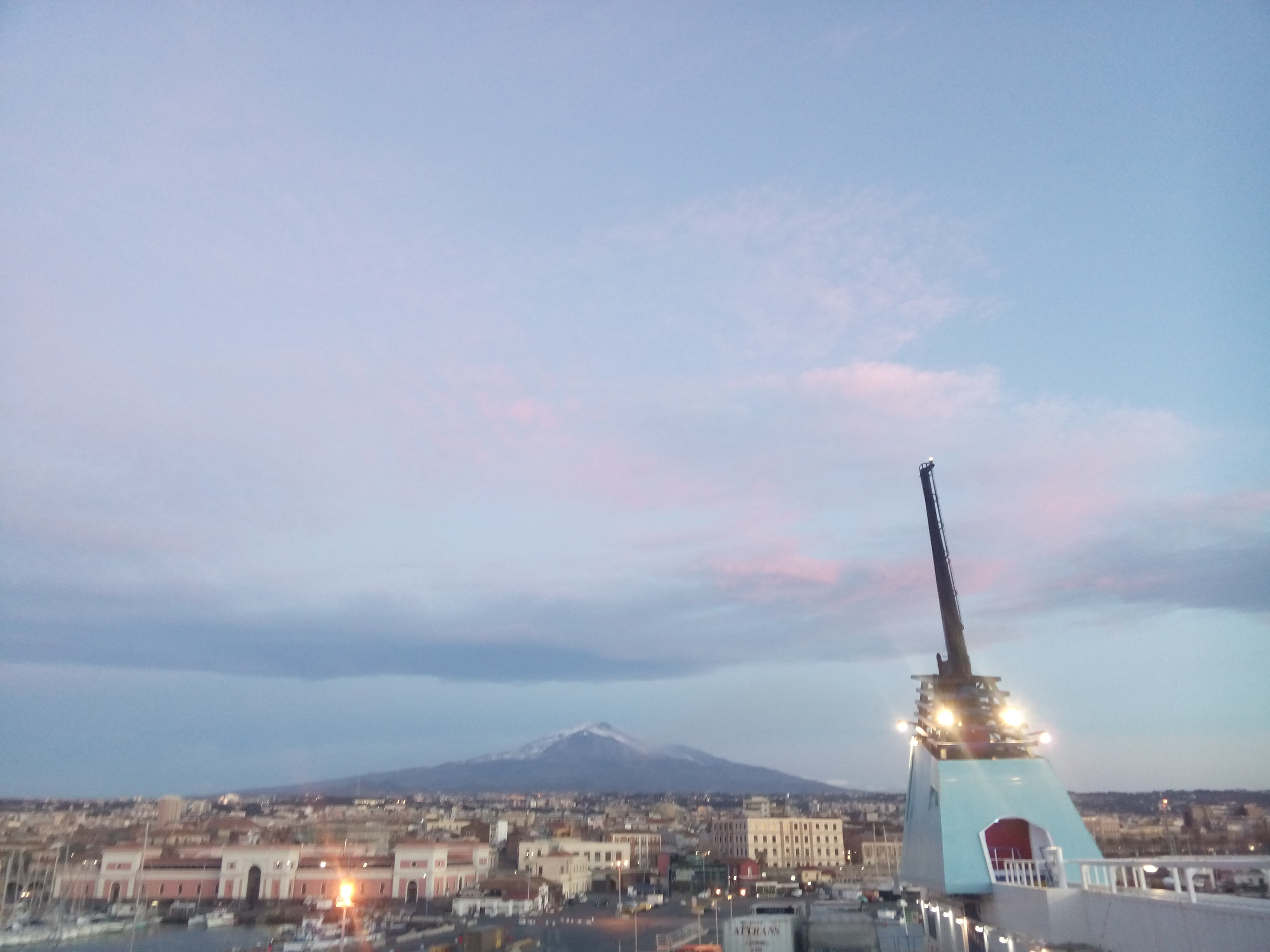 Pink and blue sky, with a sandy-coloured city (Catania) in the foreground and a dark snow-capped mountain in the background (Mt Etna)