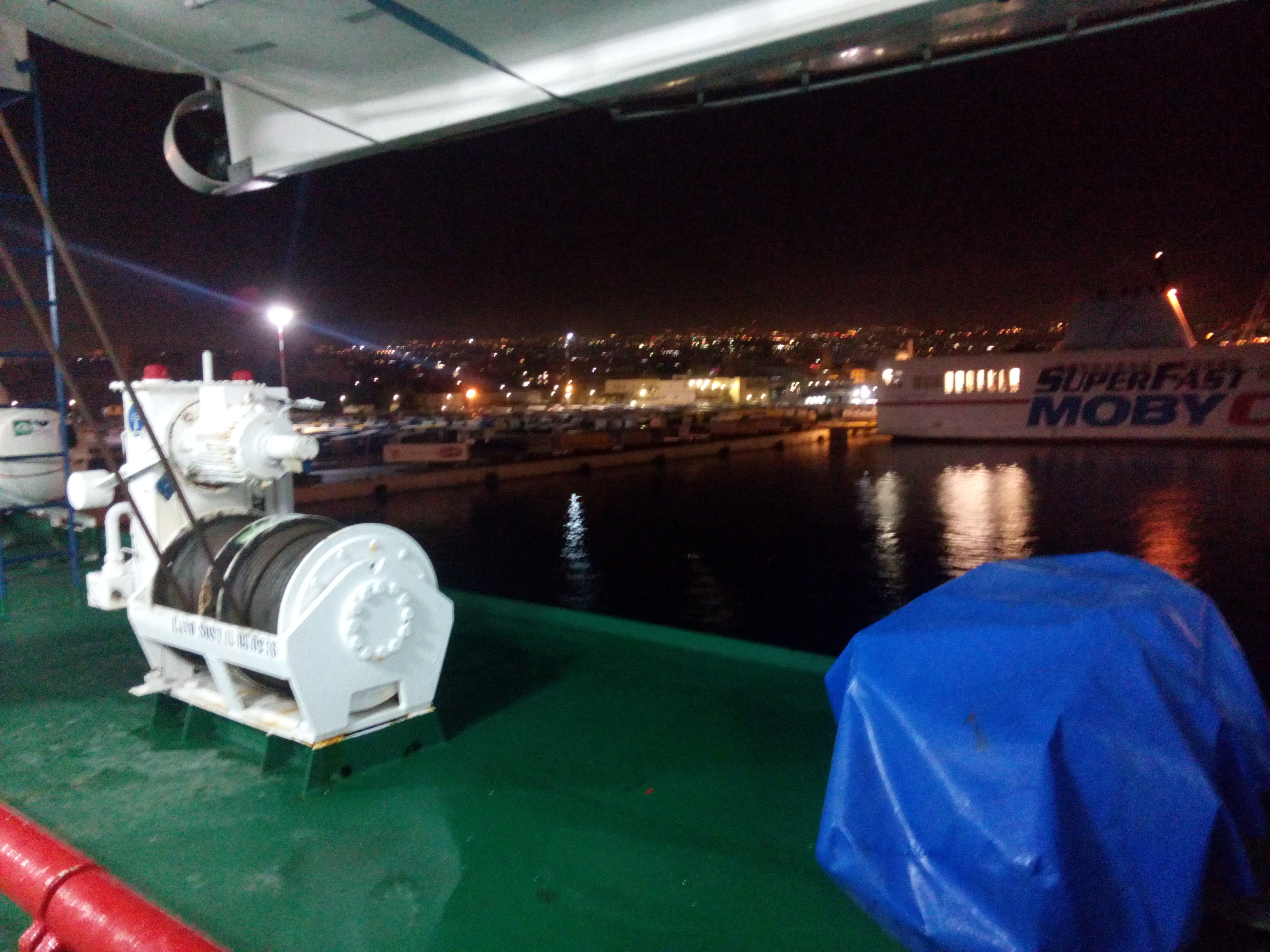 A green ferry deck with a white rope turning device. Black water and city lights in the background.