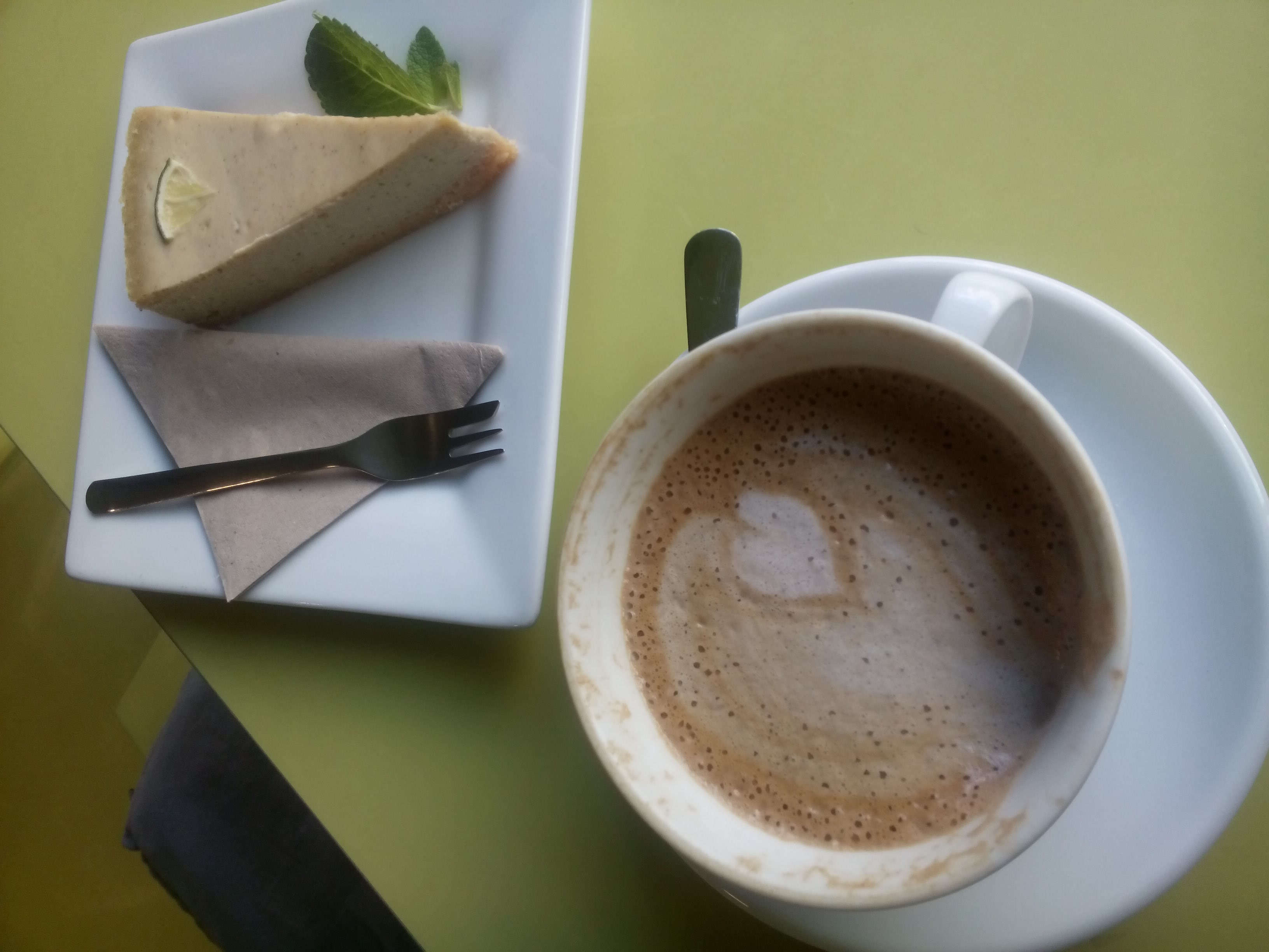 A pale green table supports a foamy cup of coffee and a slice of yellow cheesecake, from above