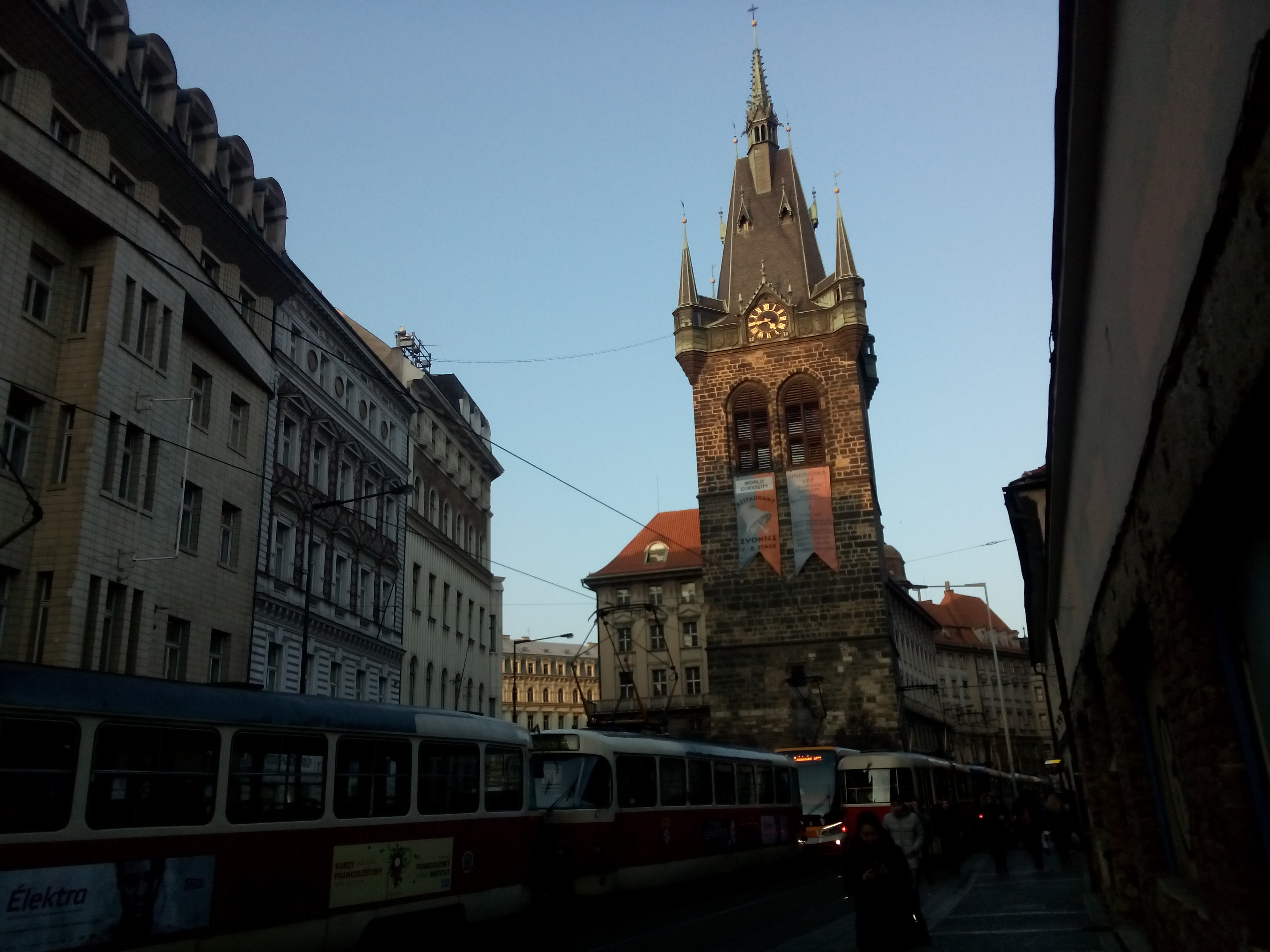 Against a blue sky, a dark brown brick church with a gothic black spire, and a tram passing in the foreground