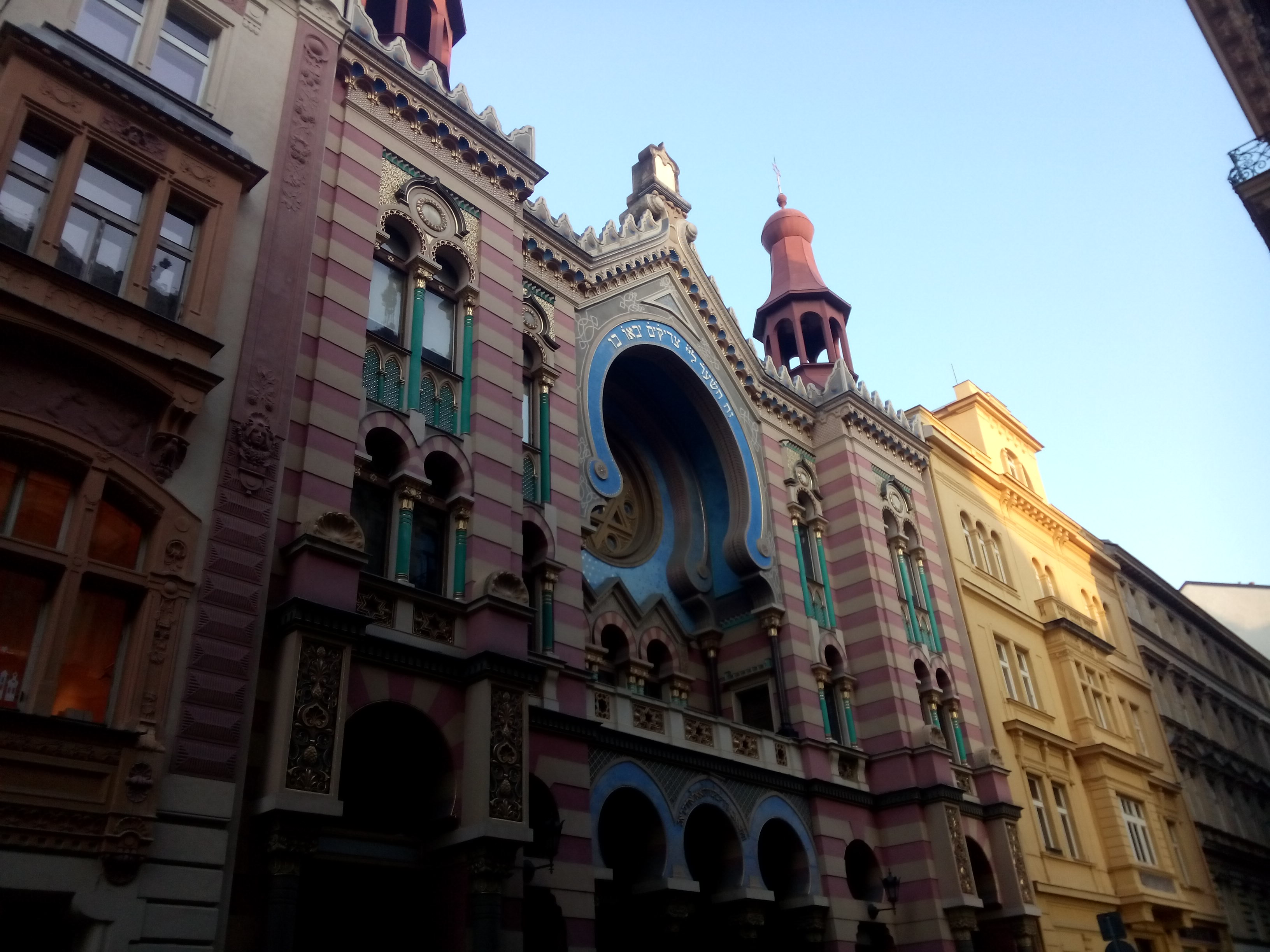 A pink and beige striped building with fancy edges and blue circular paintwork in the middle