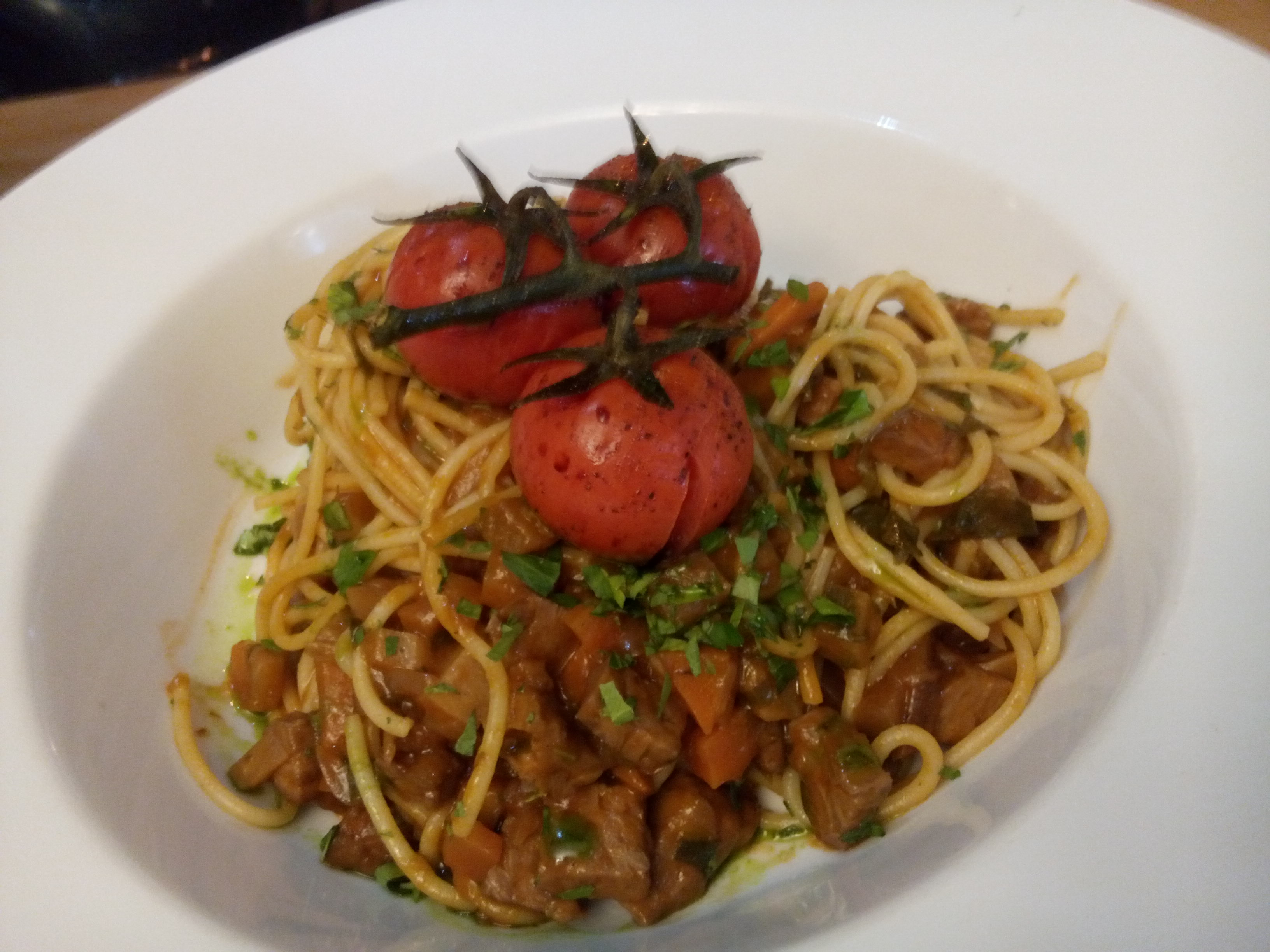 A wide white bowl with spaghetti mixed with red and brown chunky sauce, three roasted cherry tomatoes on top, still attached to the vine