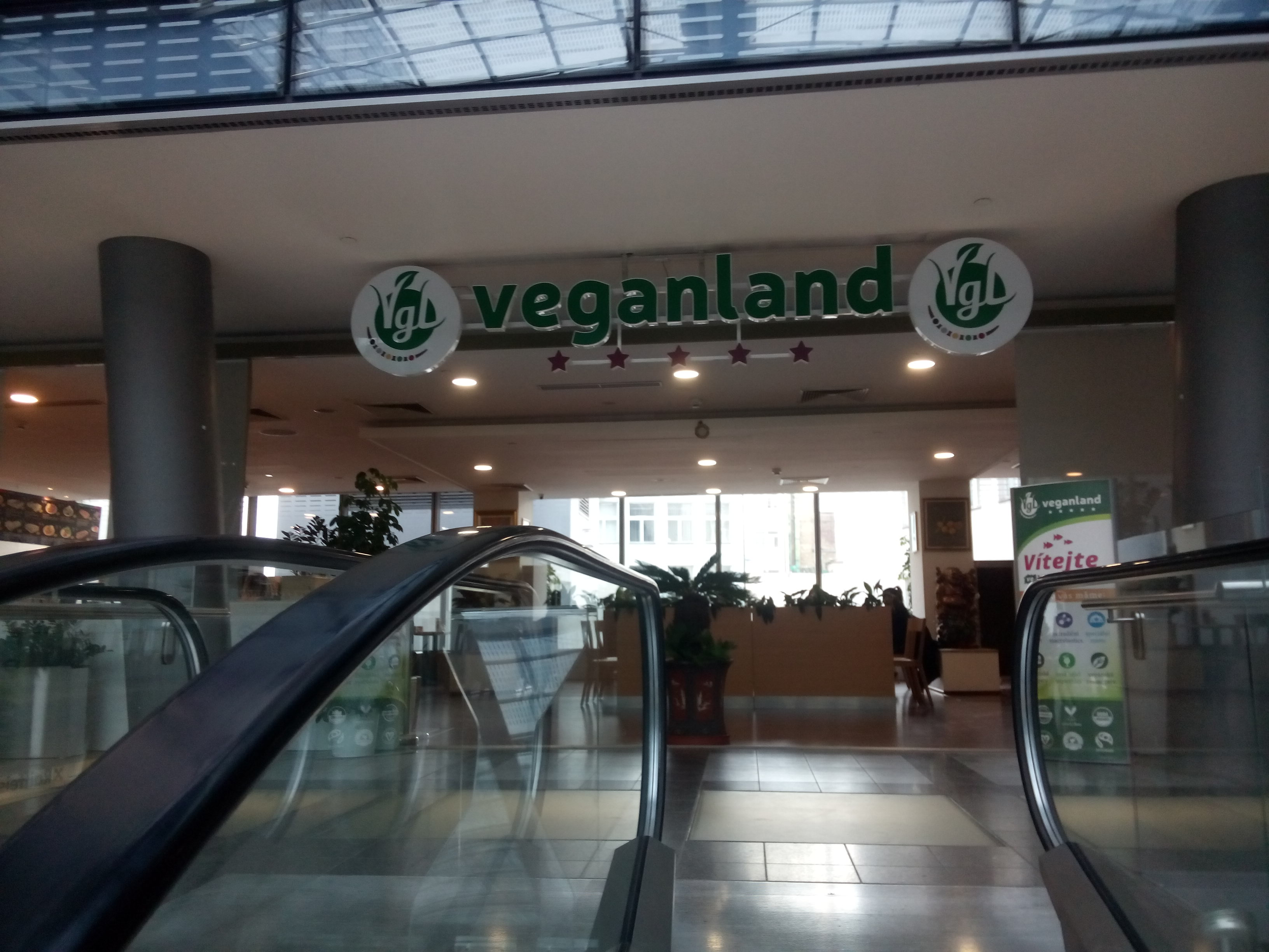 Green-lettered 'Veganland' sign at the top of a mall escalator