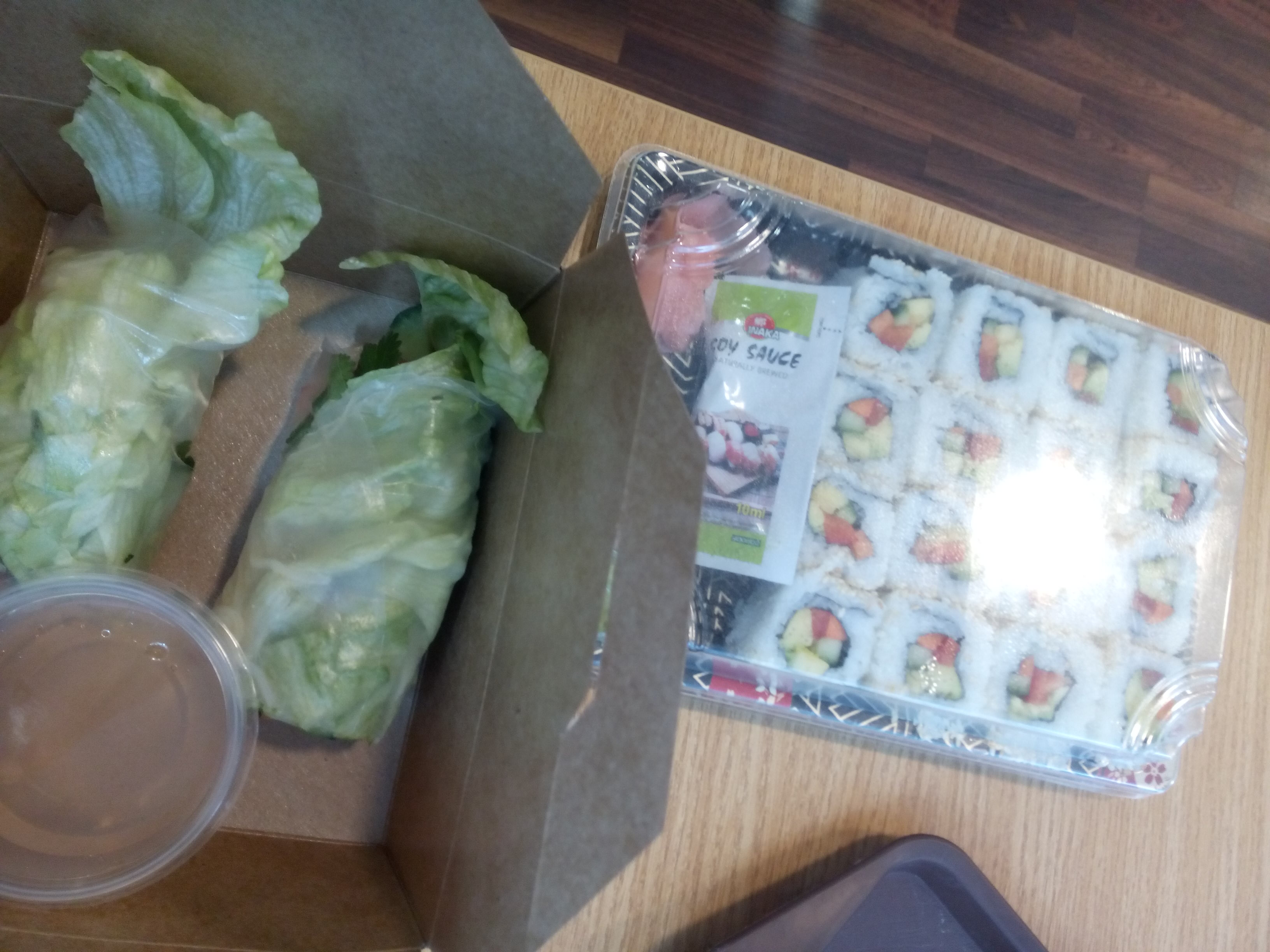 A box containing rolls of lettuce, beside a plastic tray full of colourful sushi rolls