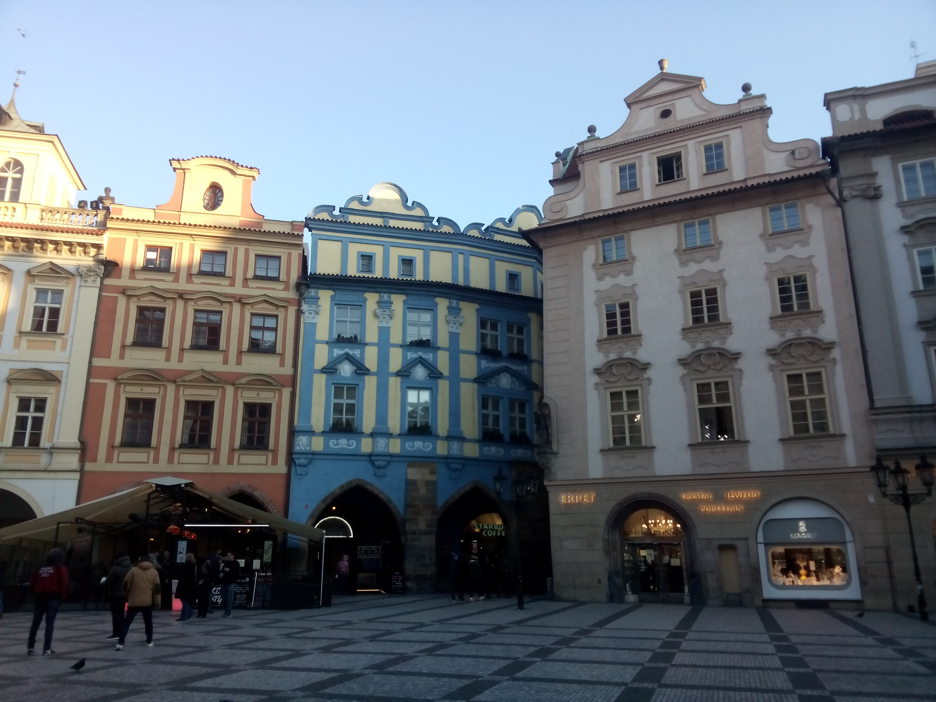 A row of fancy shaped buildings: pink, blue, beige
