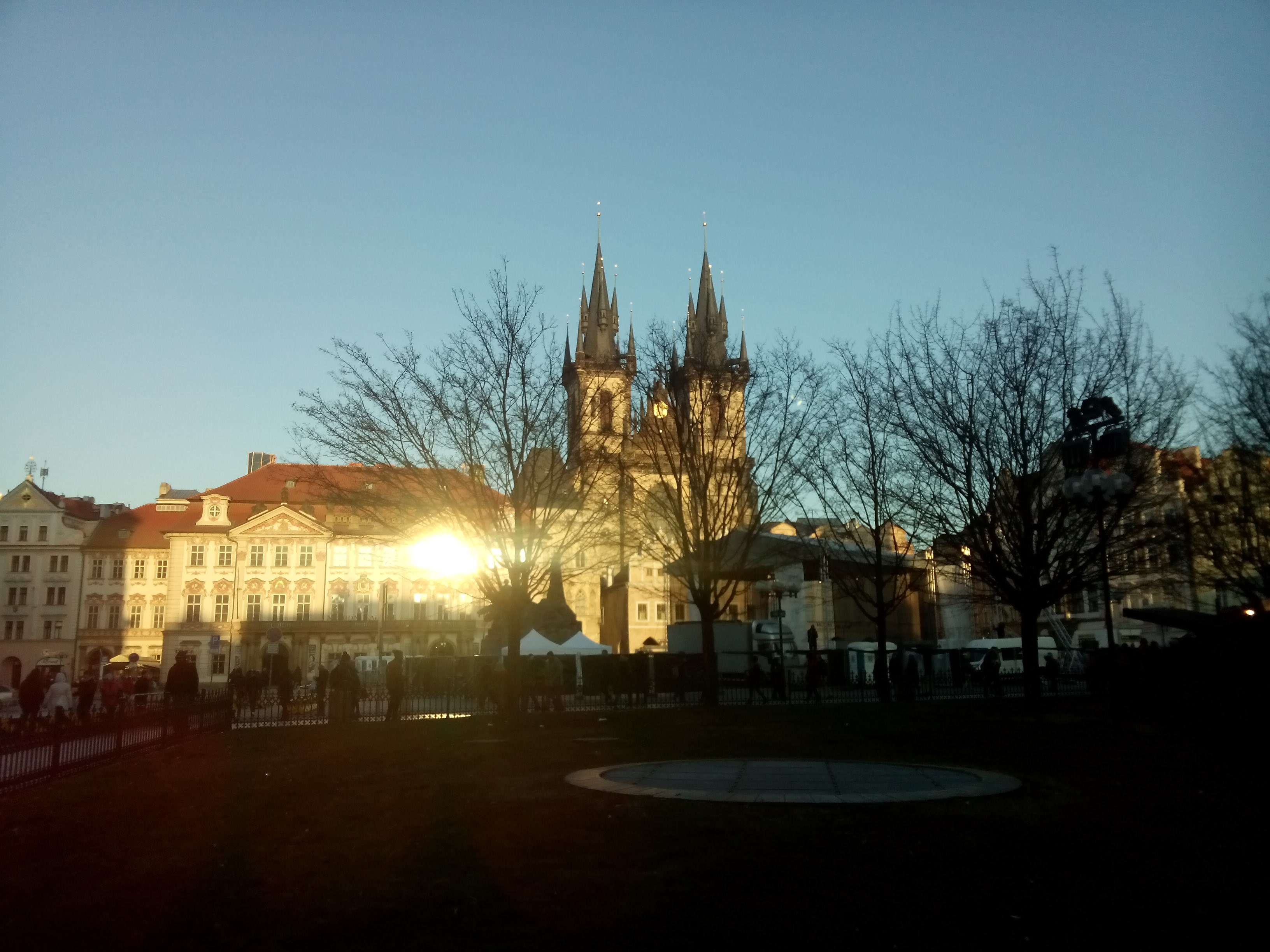 A church on the far side of a town square, with trees silhouetted against a blue sky and the reflection of a dusk sun
