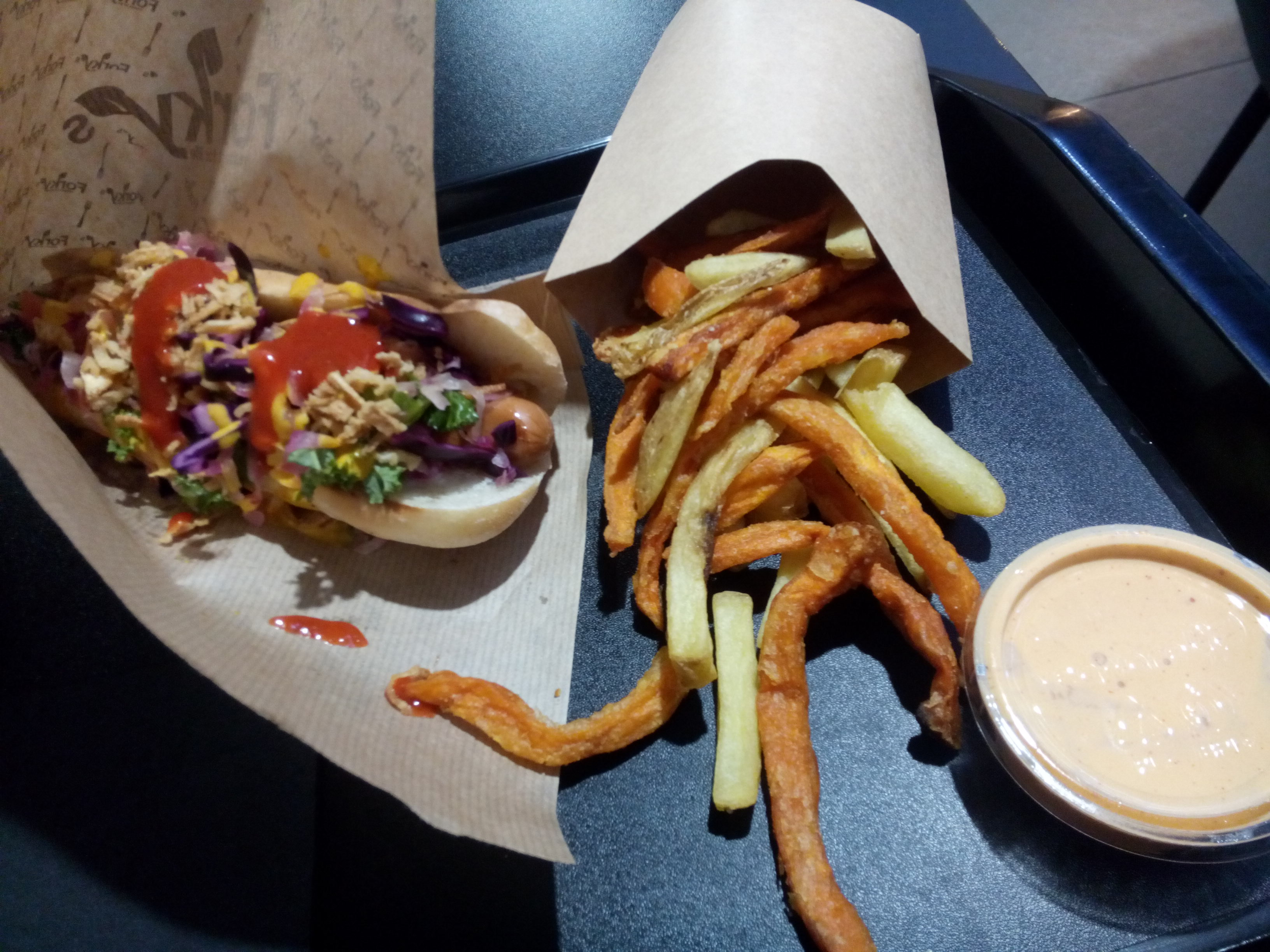 A black tray; a hotdog smothered in toppings and sauce on the left and mixed orange and yellow fries in a cardboard box on the right