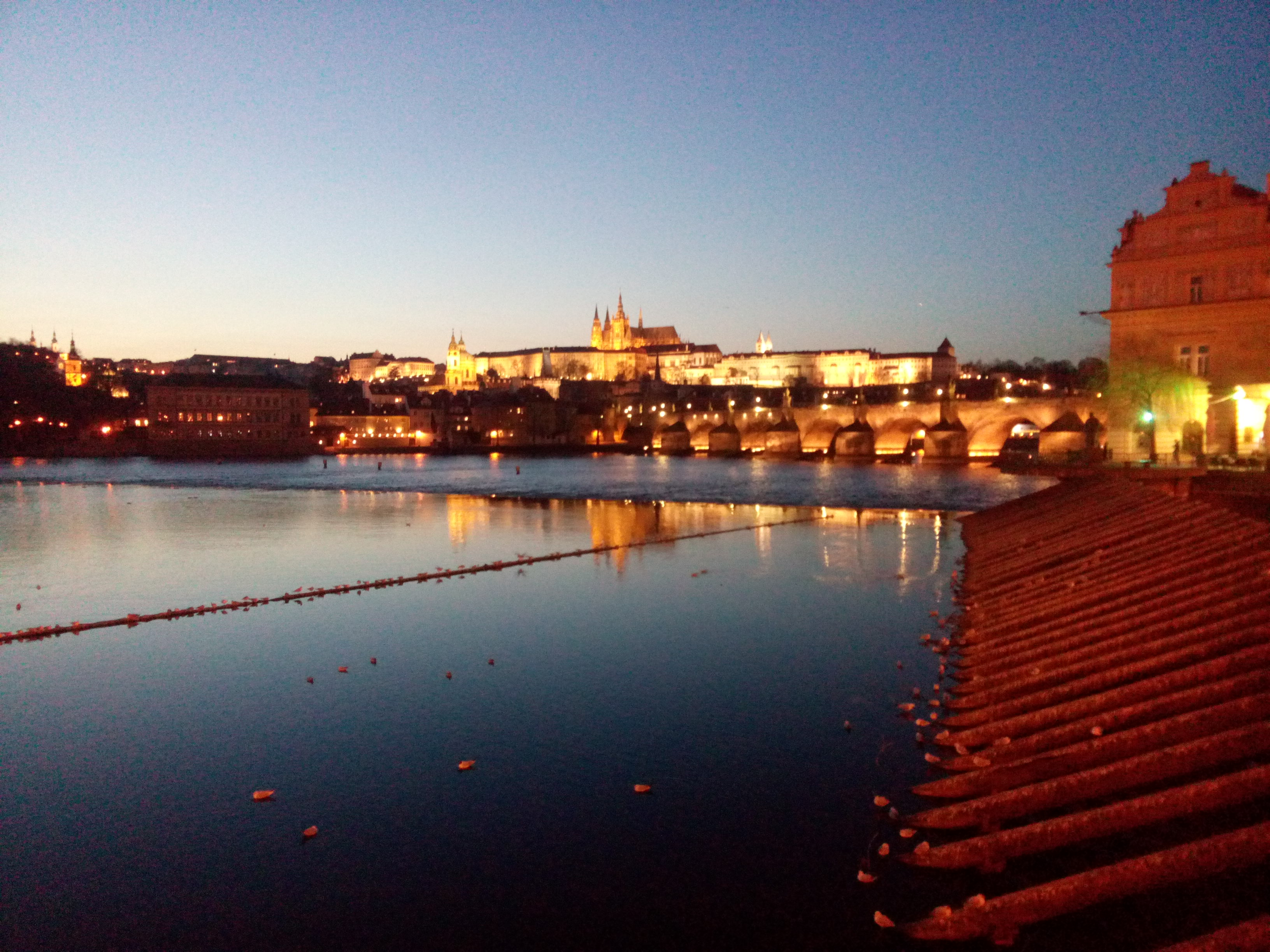 Orange lights reflect on the blue river, with the cathedral and castle on a hill in the distance