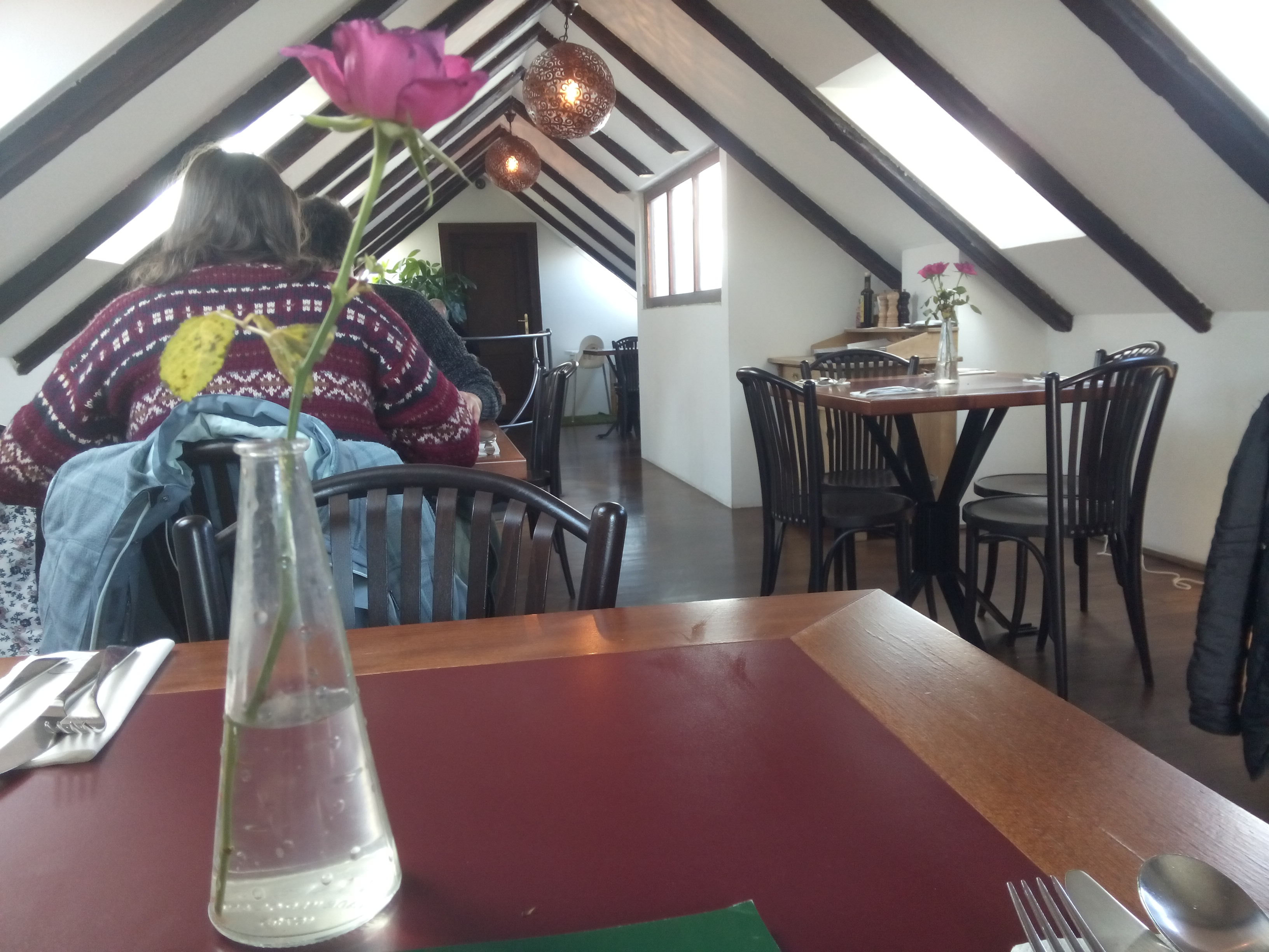 A restaurant interior with red tables and a pink rose in a vase in the foreground. The background is white walls with dark wooden beams angled into a triangular roof