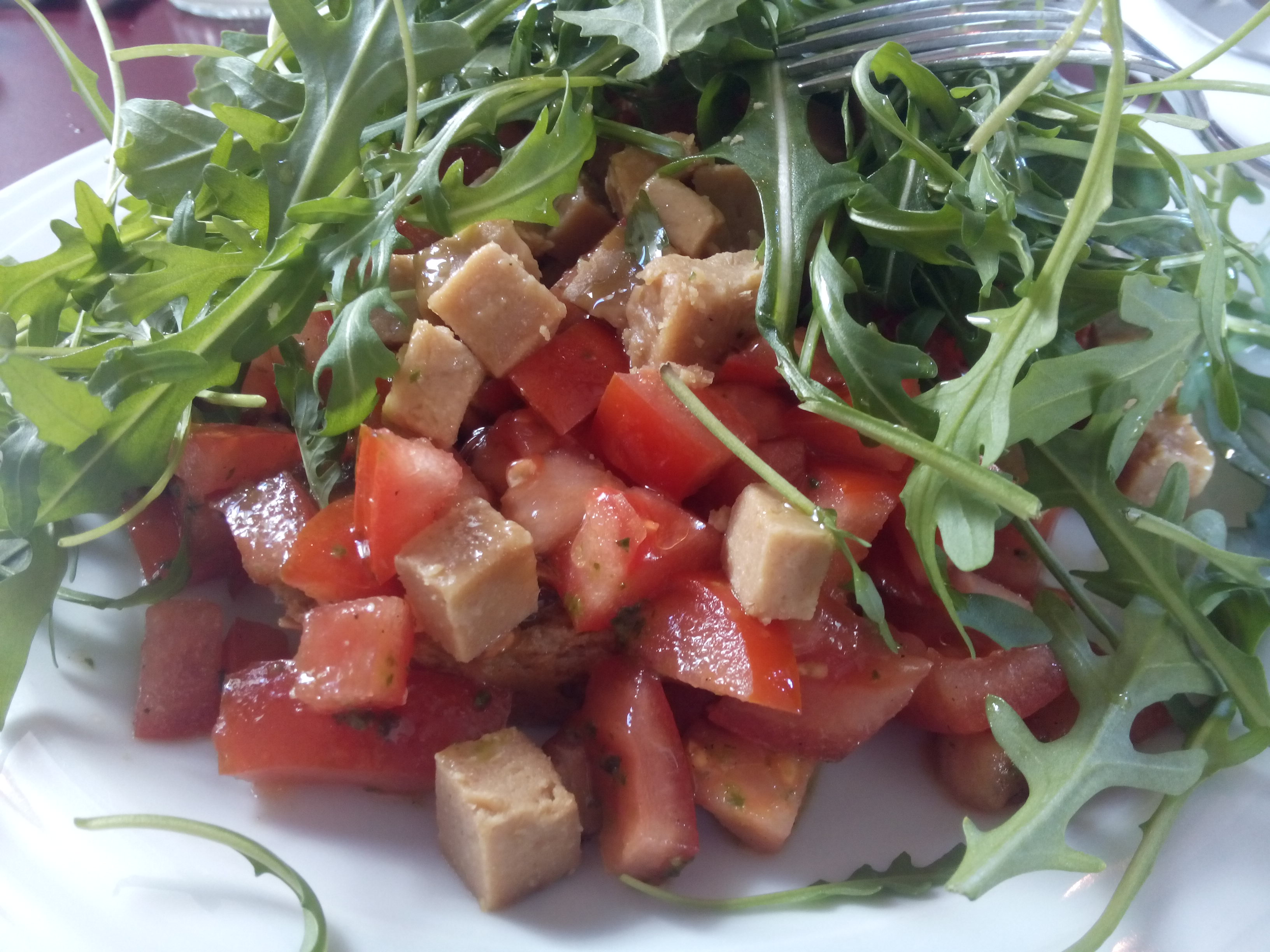 A mountain of rocket shrouds chunks of red tomato and brown cashew 'cheese'