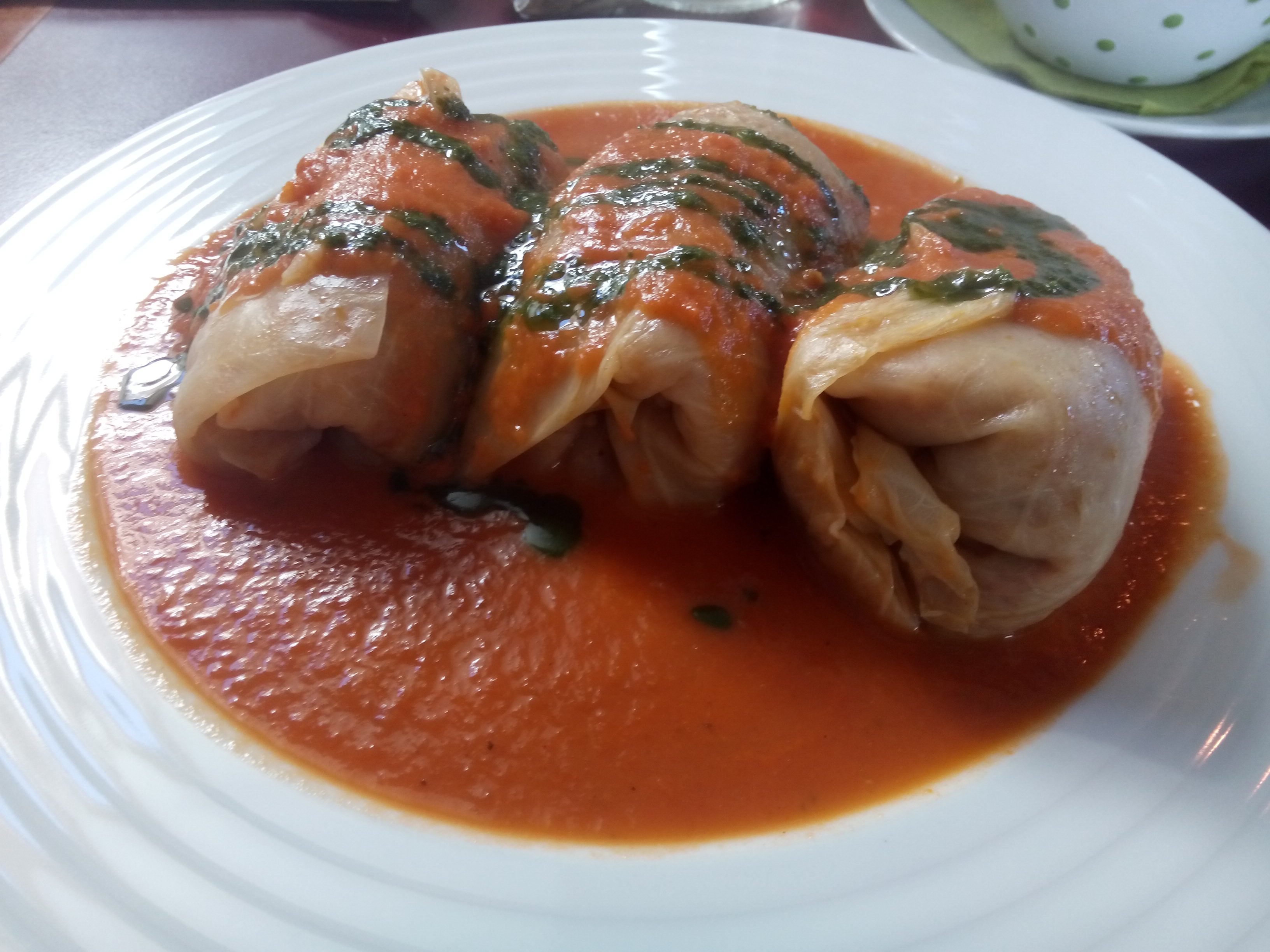 Three cylindrical stuffed cabbage leaves drown in red sauce on a white plate