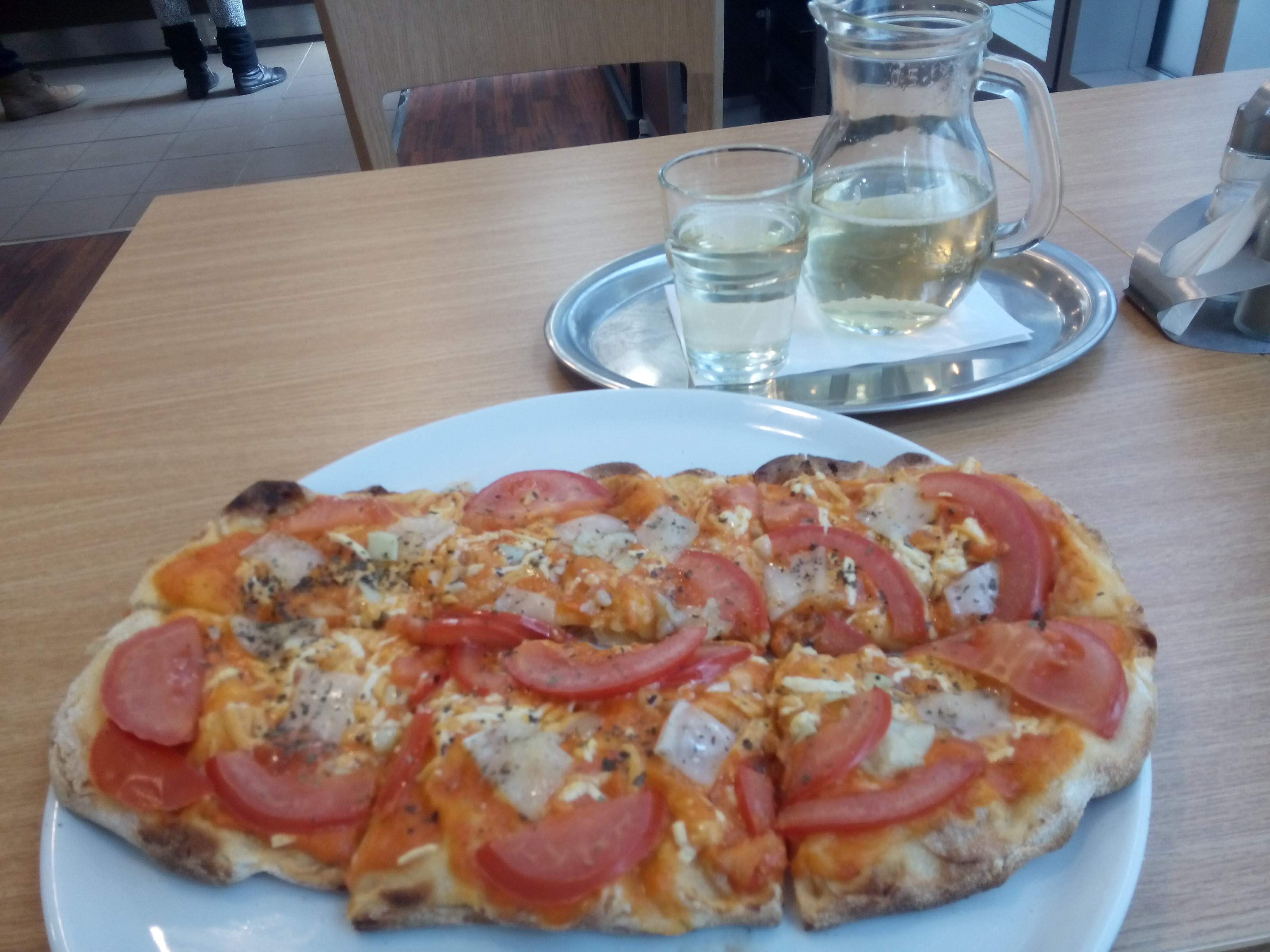 A tomato-covered pizza on a white plate, on a brown table