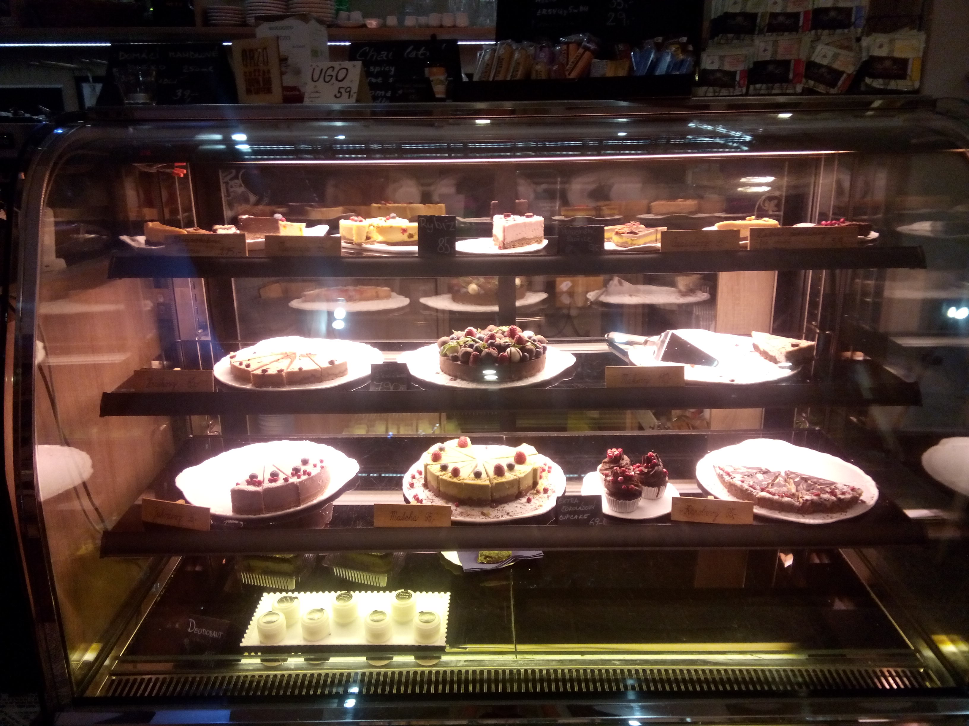 A counter with four shelves full of cakes, dramatically lit