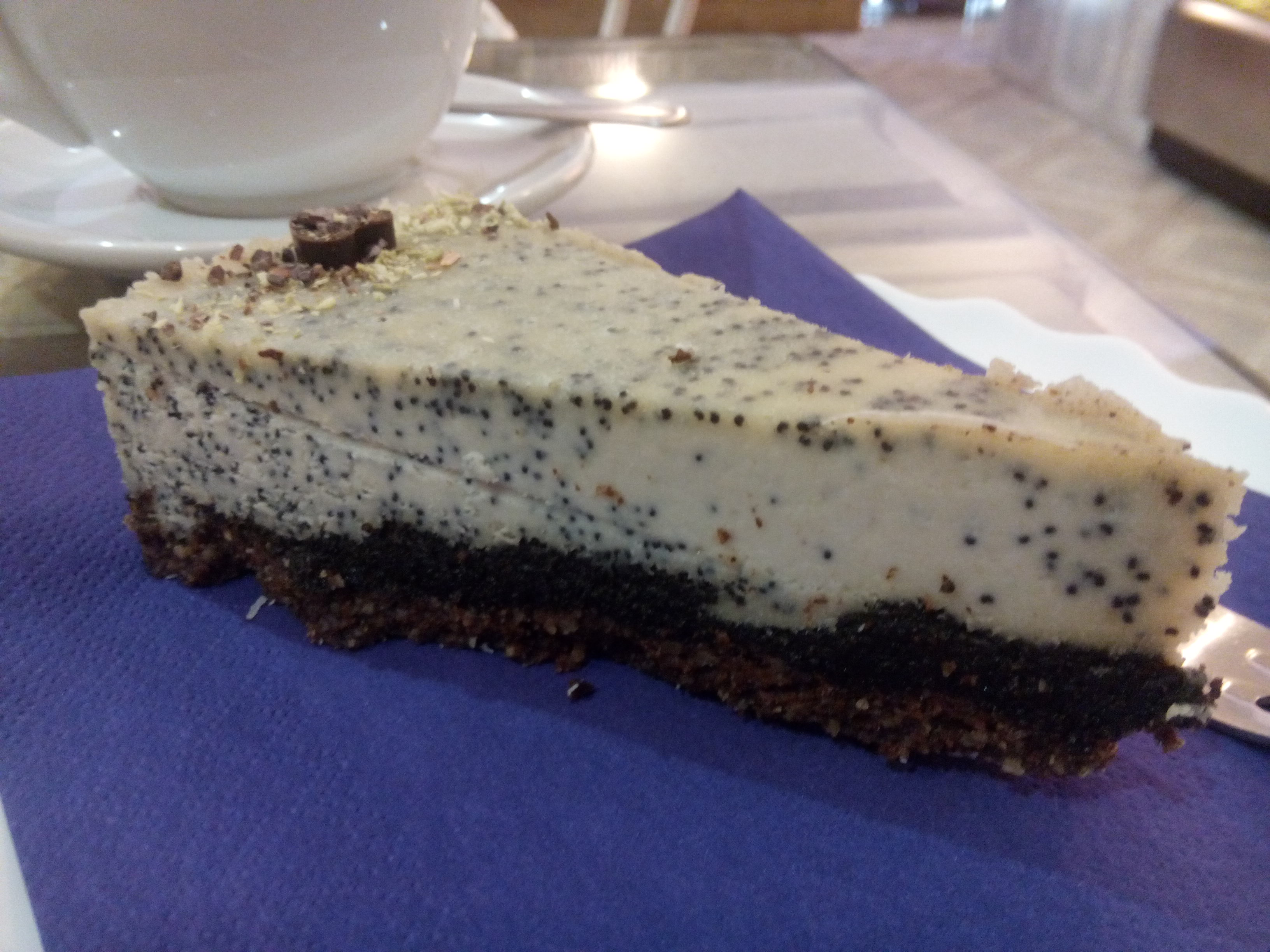 A white cake with a brown biscuit base and vanilla pods speckled throughout, on a blue napkin