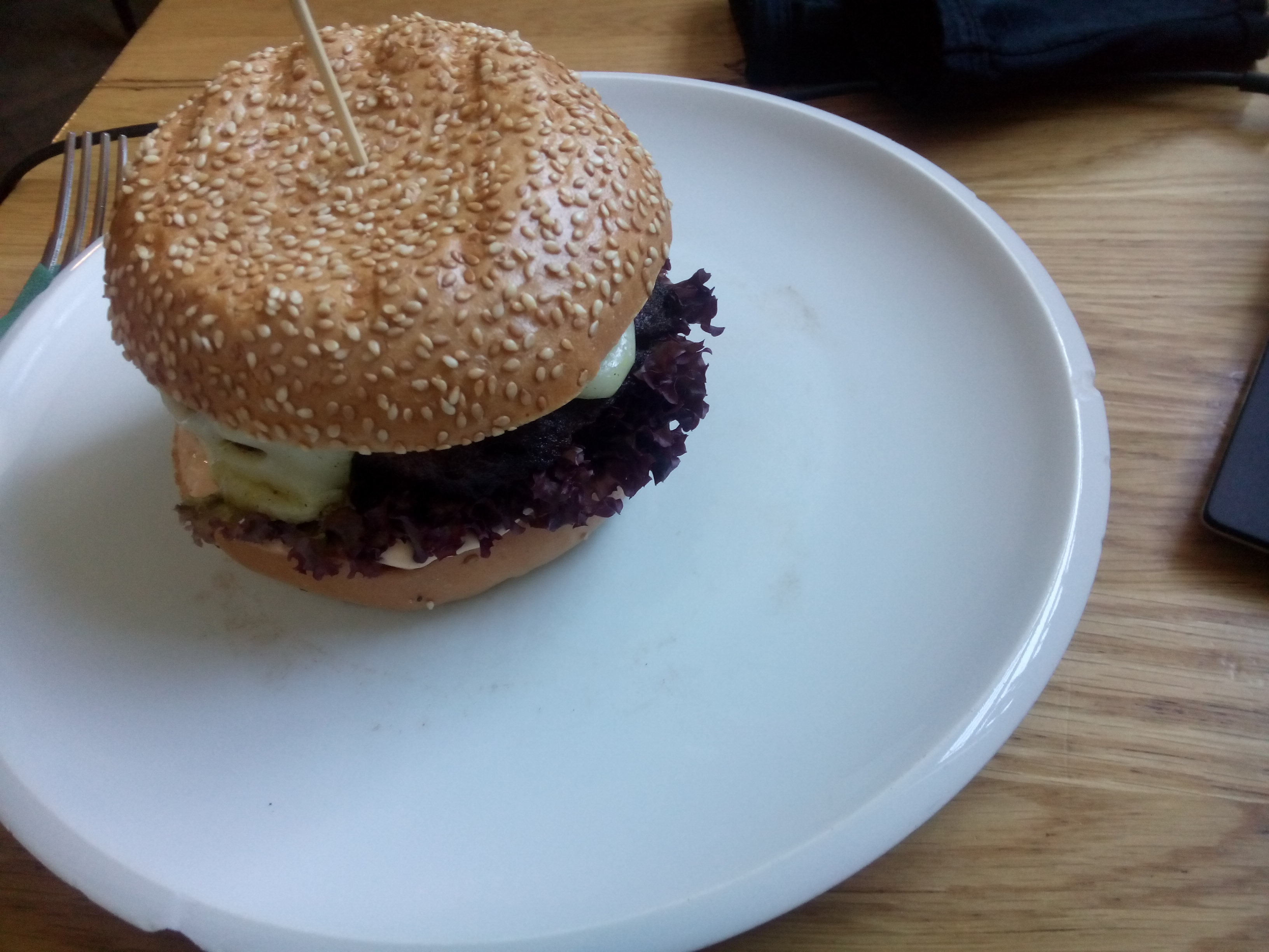 A white plate on a wooden table, with a seedy bread bun with cheese and red lettuce poking out of the side