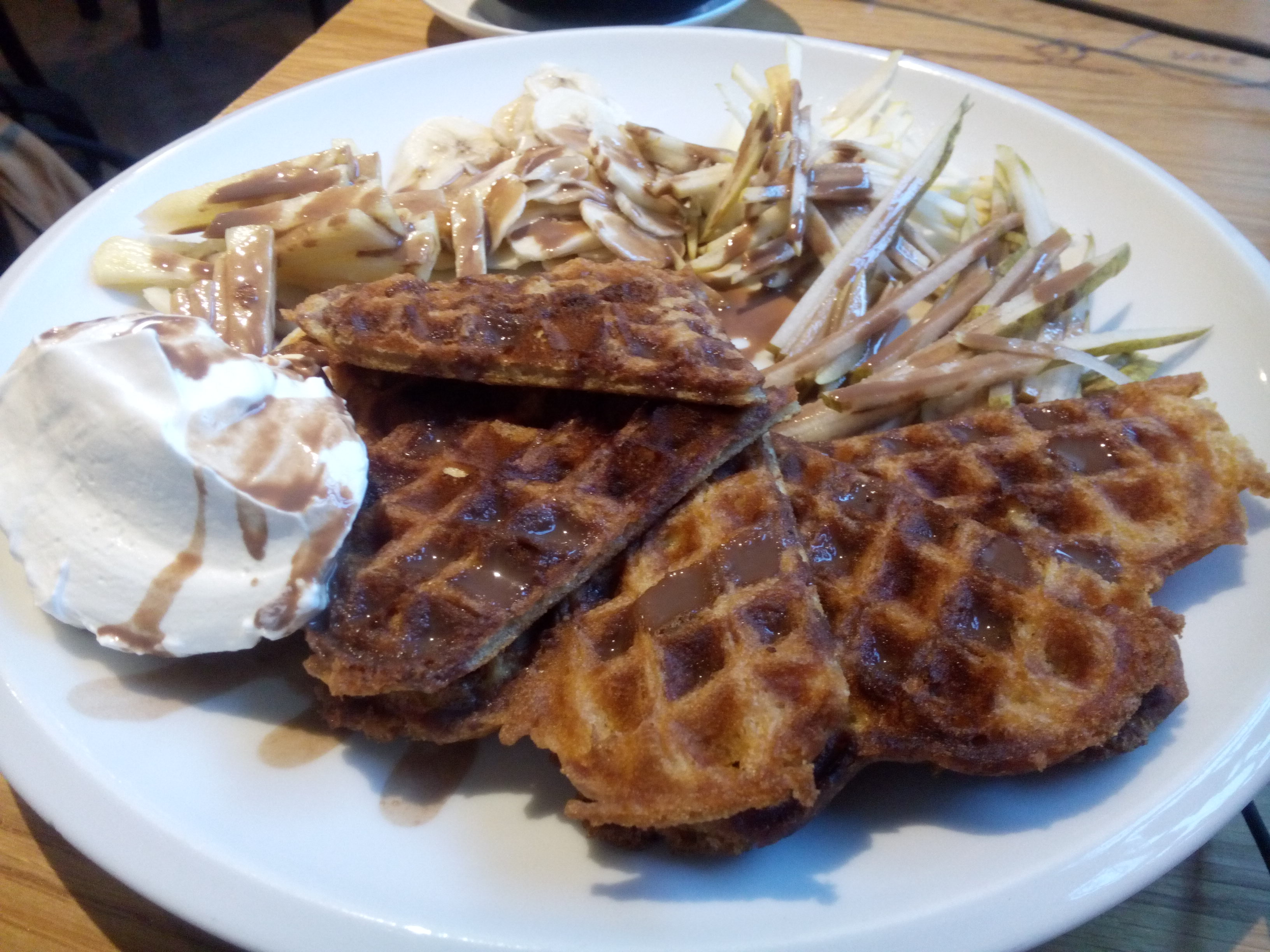 A white plate packed with waffles, cream, chopped apple and chocolate sauce