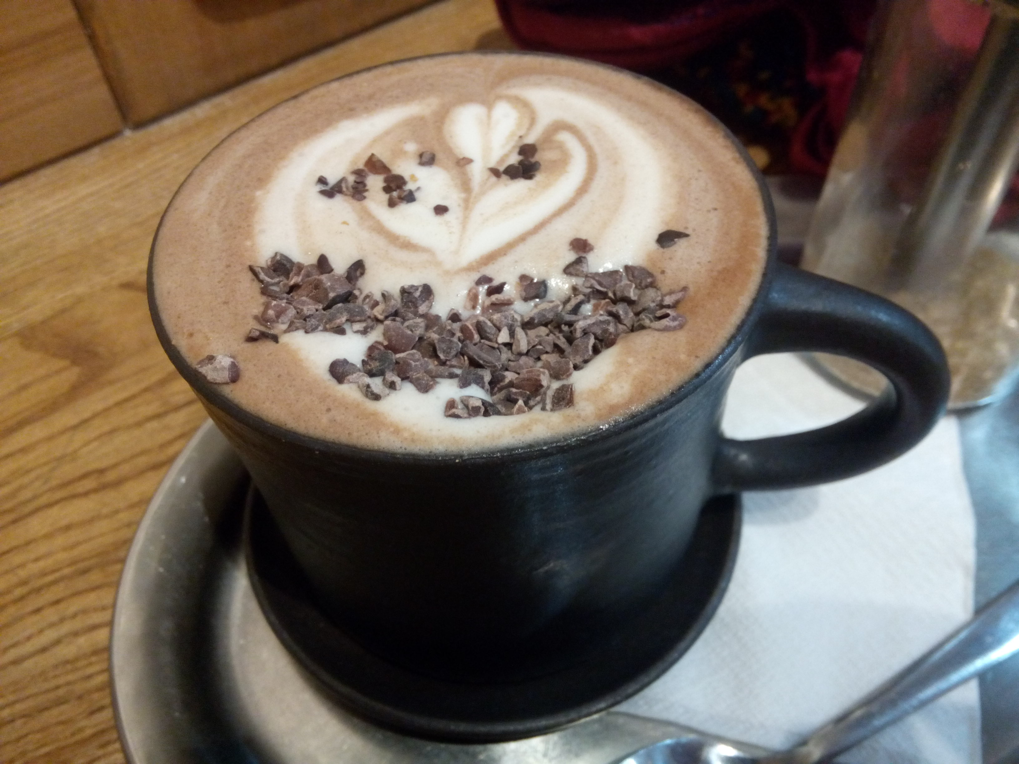 A black mug with brown and white foam swirls of milk and cacao nibs