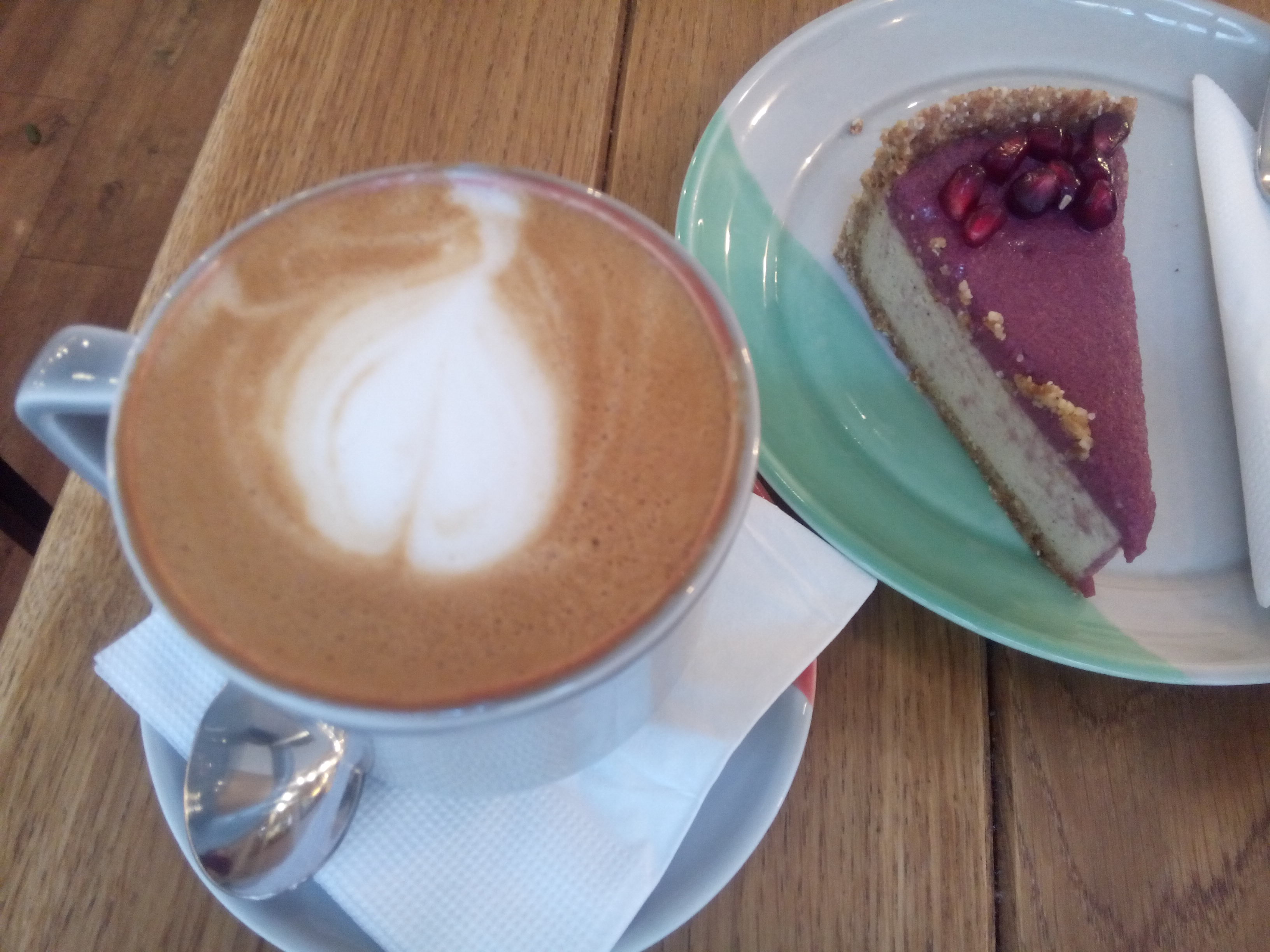 A big foamy cappuccino and a slice of purple and white cheesecake with pomegranate seeds on top