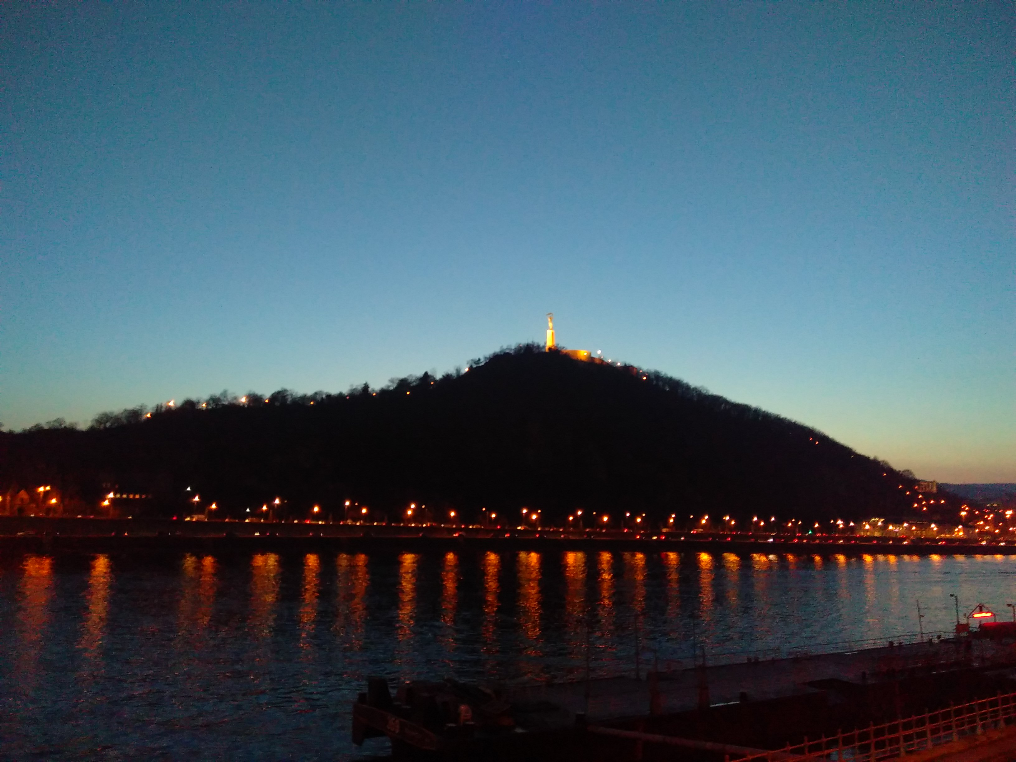 A dark hill on the far side of a dark blue river, with orange lights reflecting and a white tower on top of the hill