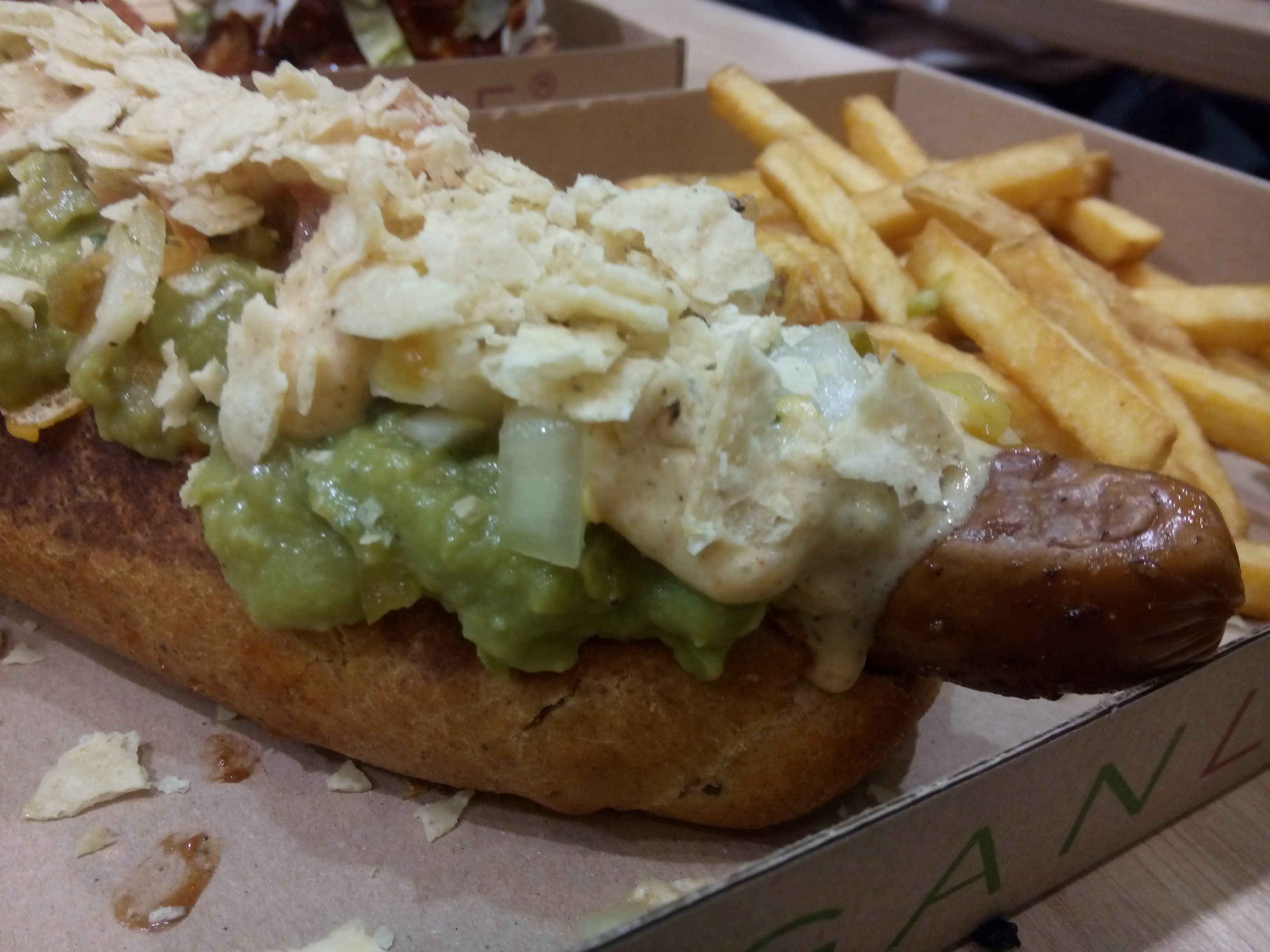 An overflowing hotdog with avocado and cheesey sauce, fries to the right