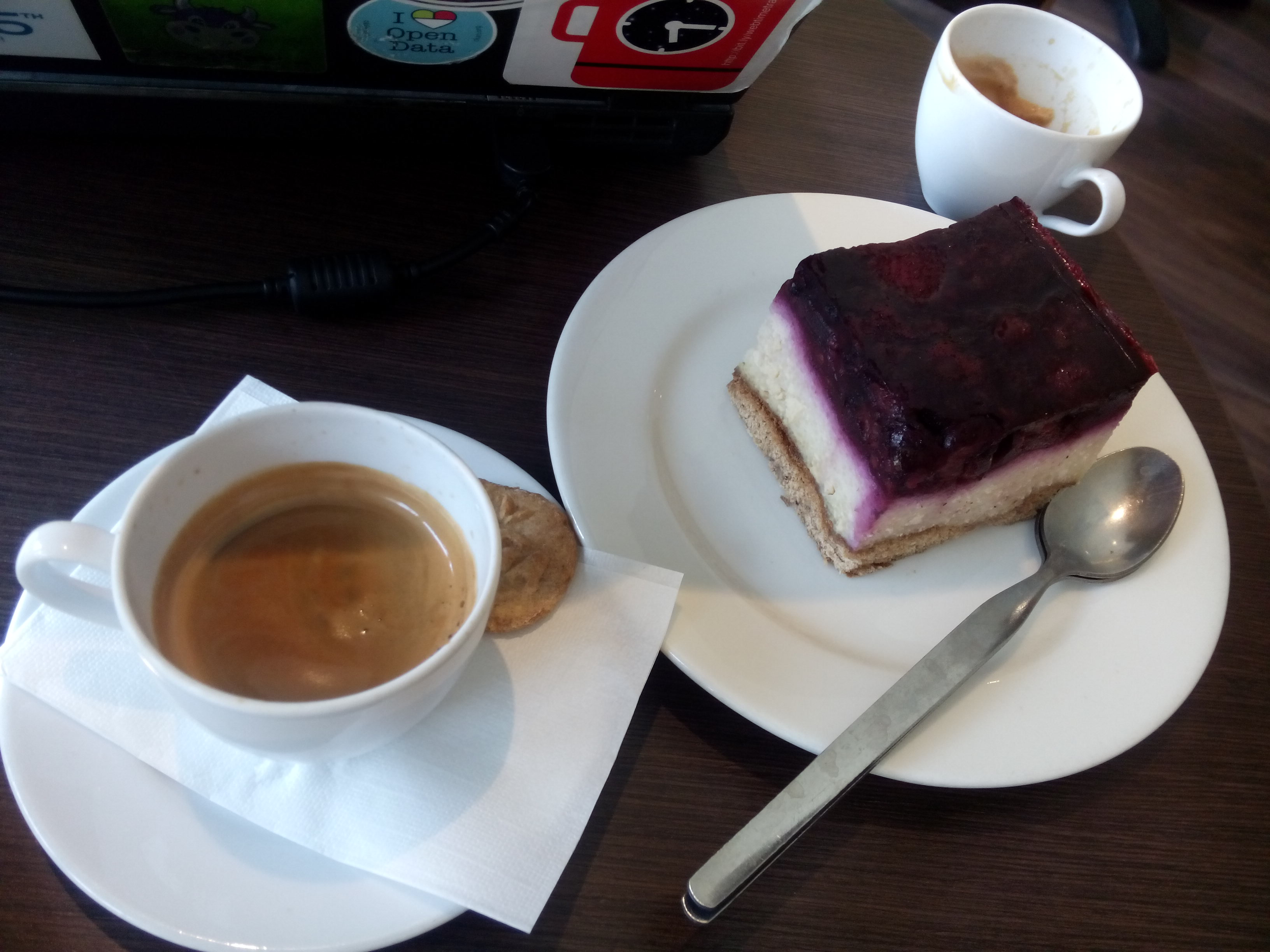 A cup of coffee next to a purple and white bouncy looking cake on a plate