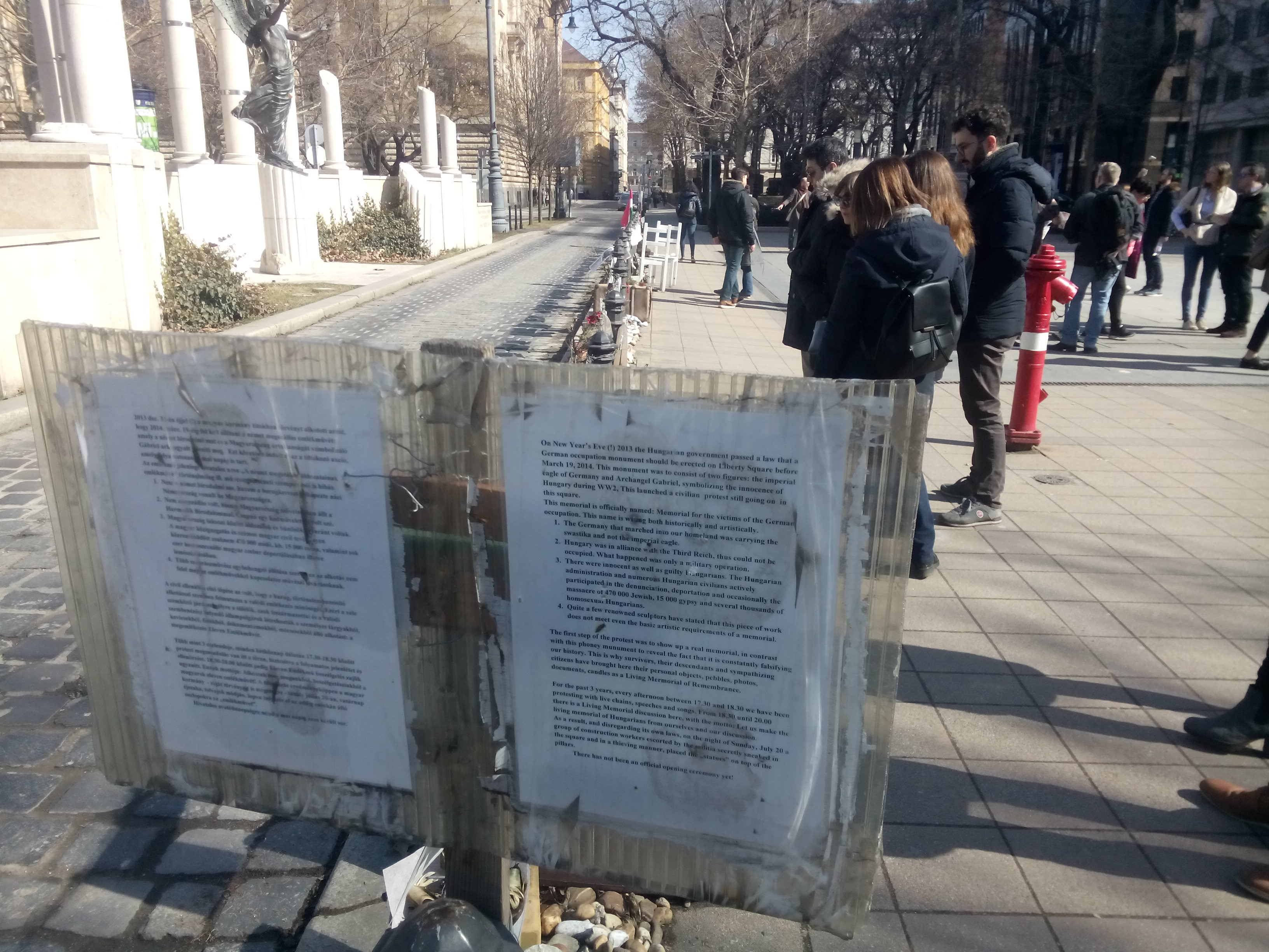 A typed sign on a post against a long row of memorials, while small groups of tourists read them