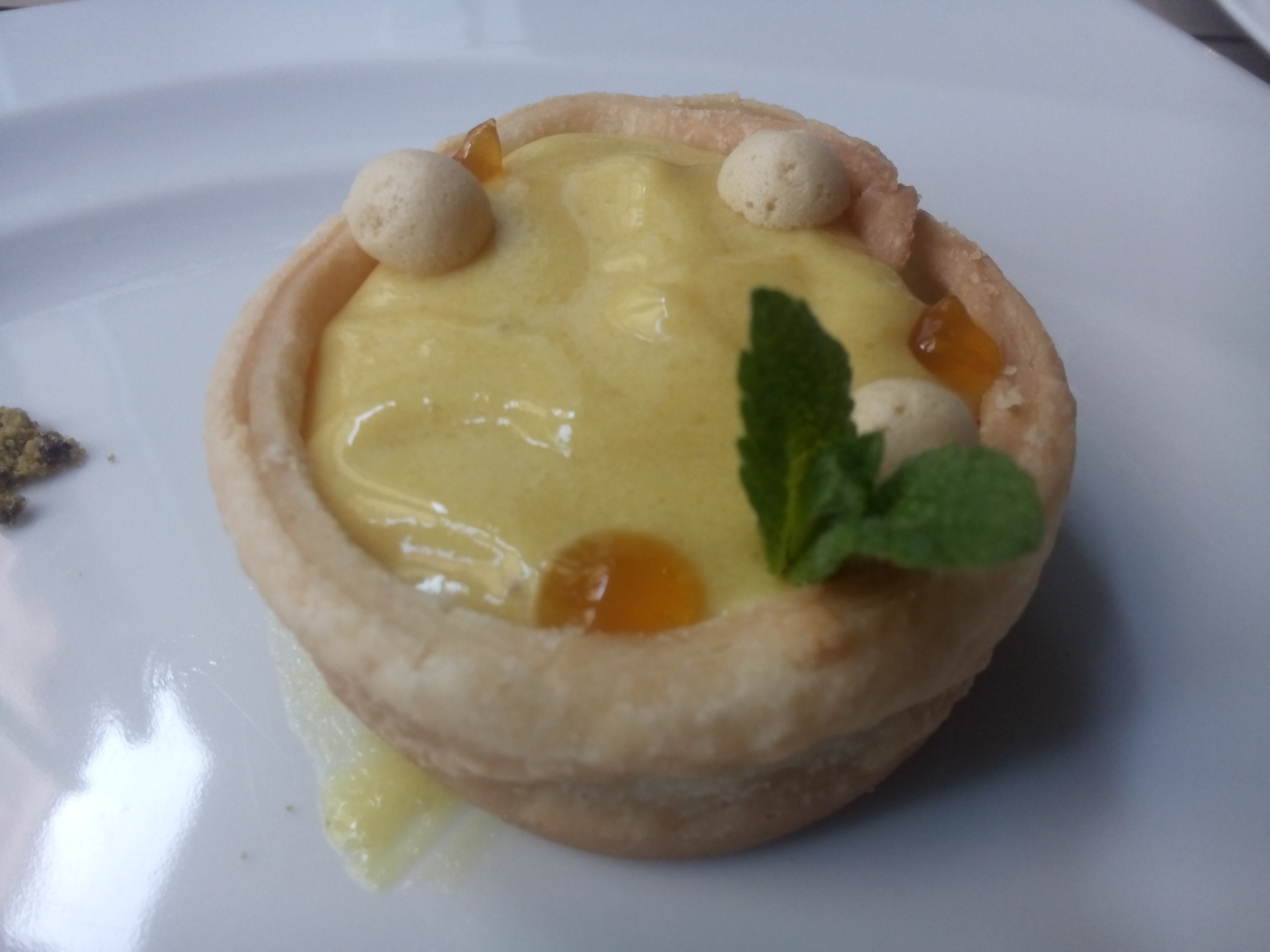 Small crusted tart with yellow cream and a spring of mint