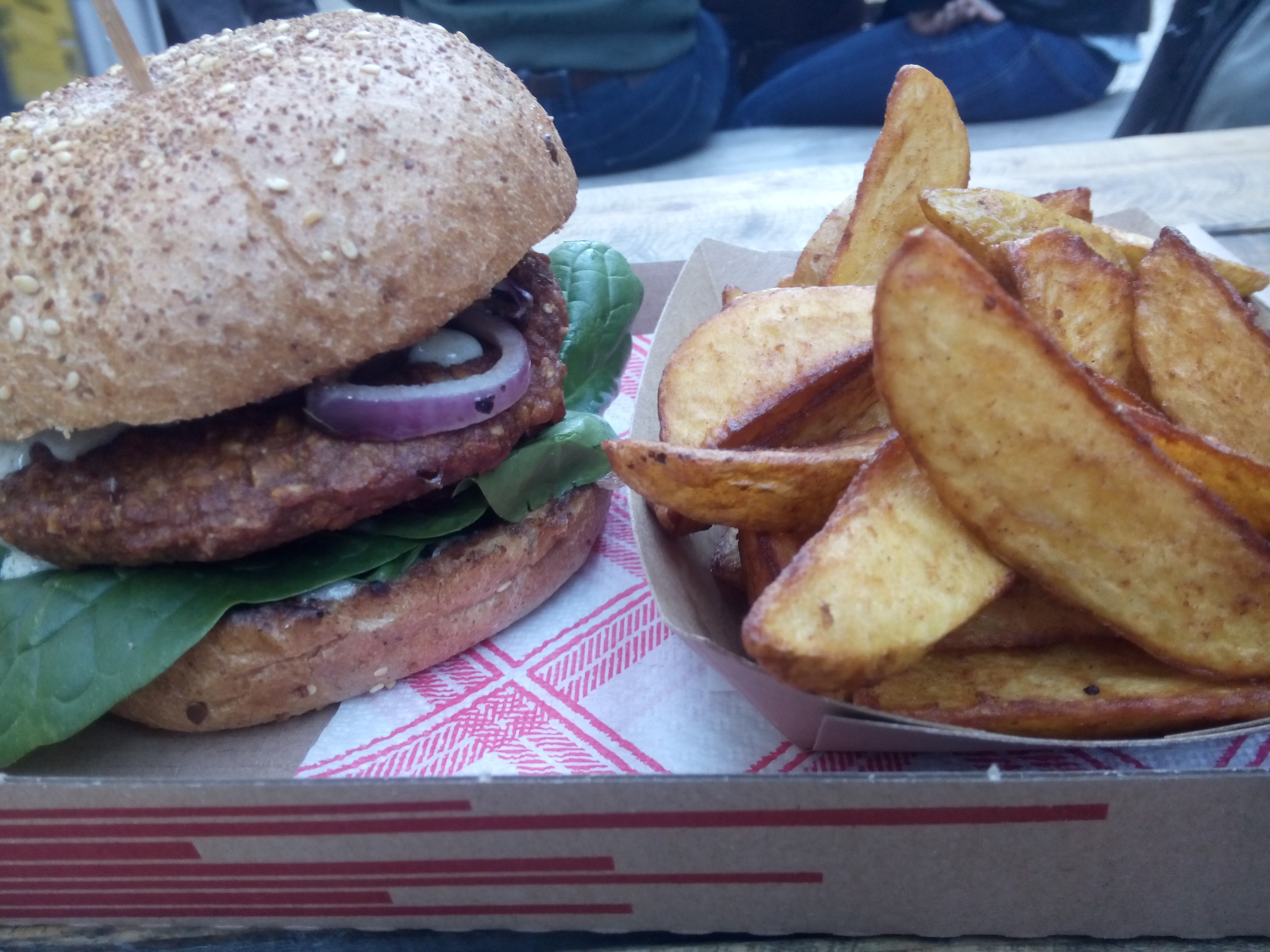 A burger poking out of a seedy bread bun with spinach and red onion, beside a cardboard tray of potato wedges
