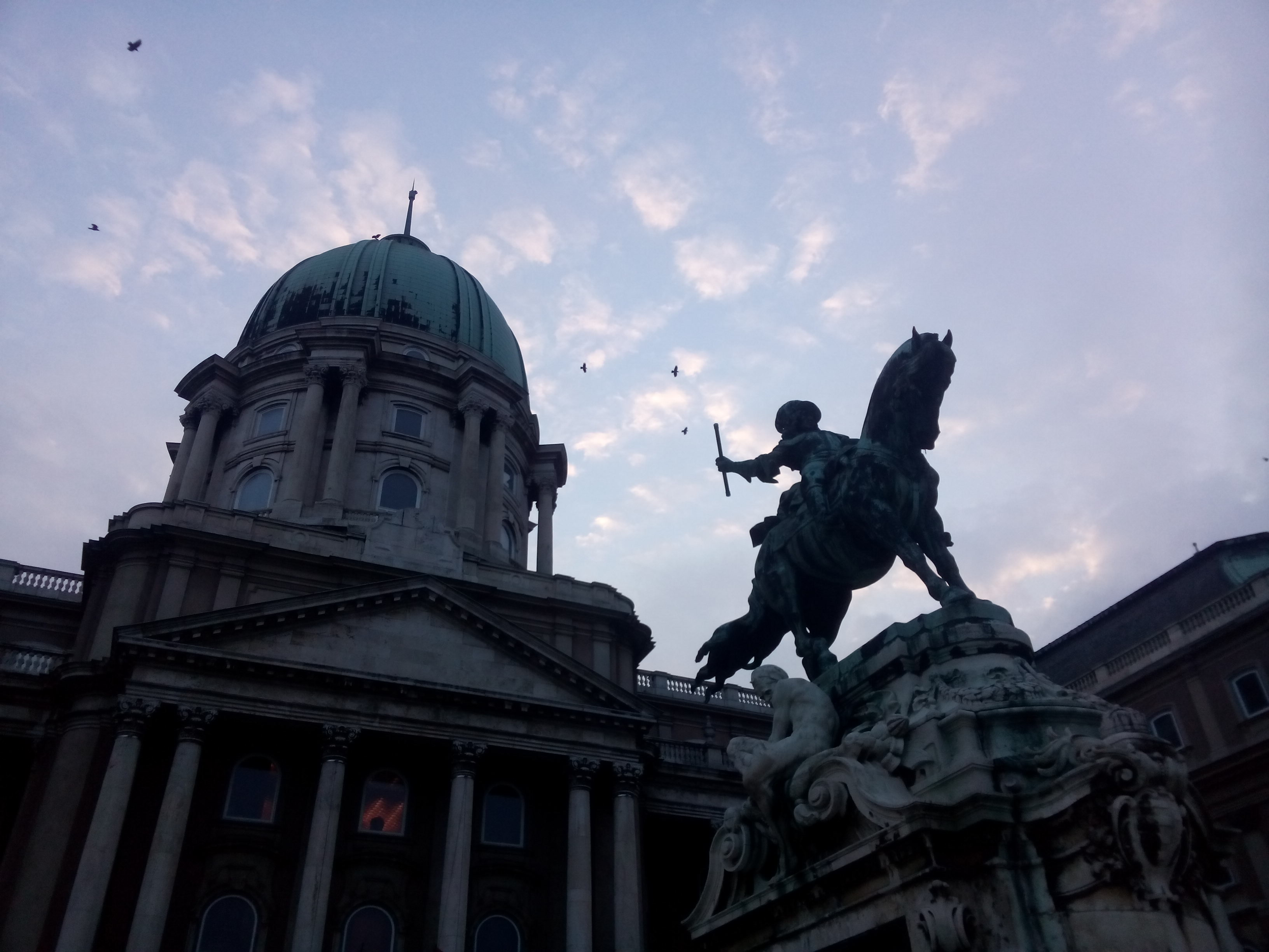 A building with a green dome behind a statue of a man on a horse with a sword