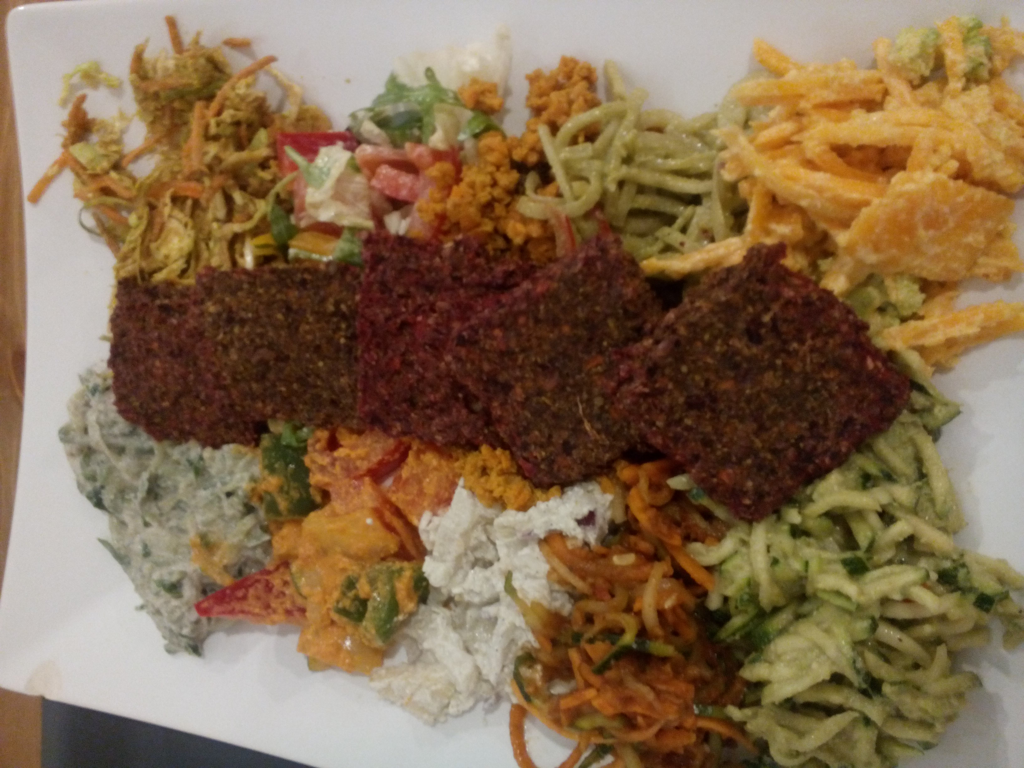 A plate with a line of small square crackers down the middle, and various colourful salads in blobs either side