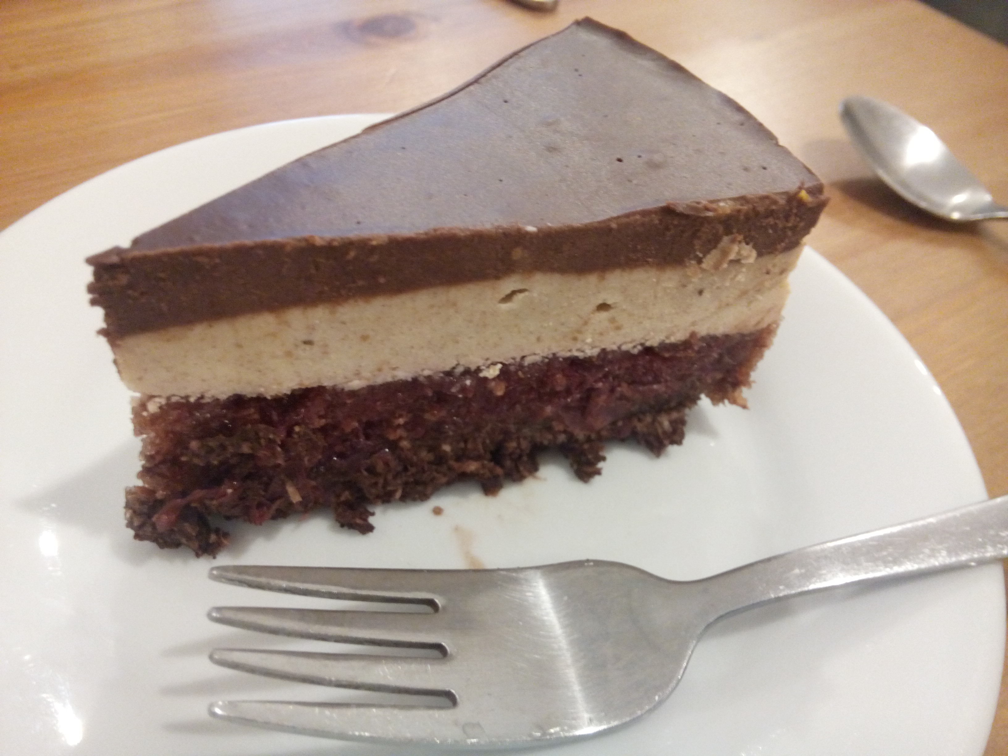 Cake with a chocolate layer, a cream layer and a purple cherry layer