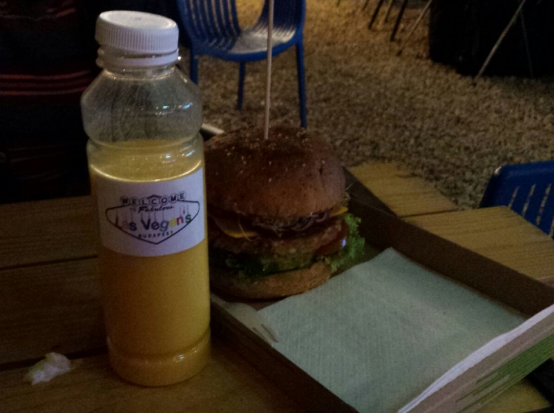 A plastic bottle three quarters full of yellow liquid, beside a cardboard tray with a sturdy looking burger on