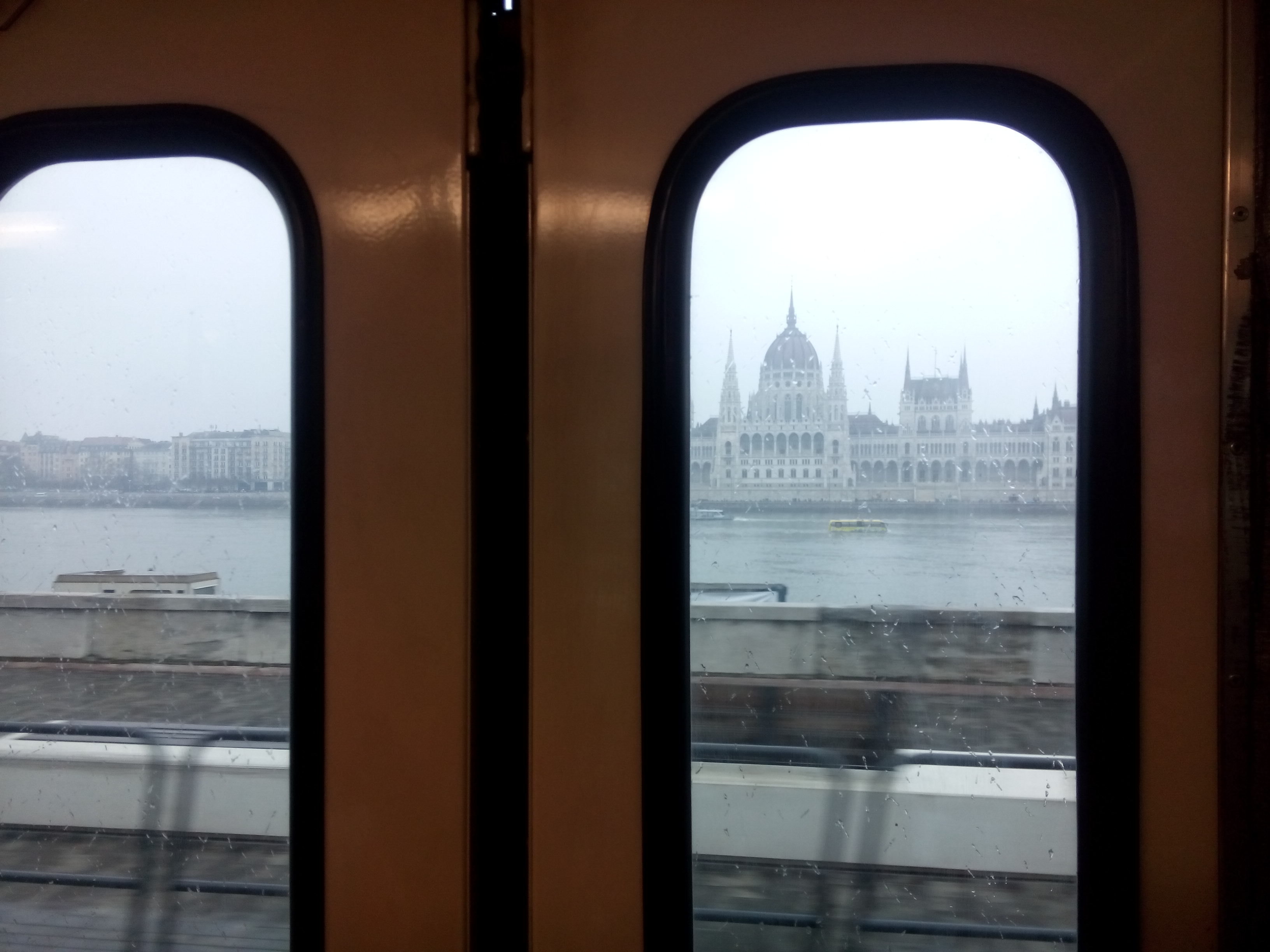 Inside window of a tram frames a grand white building across a river